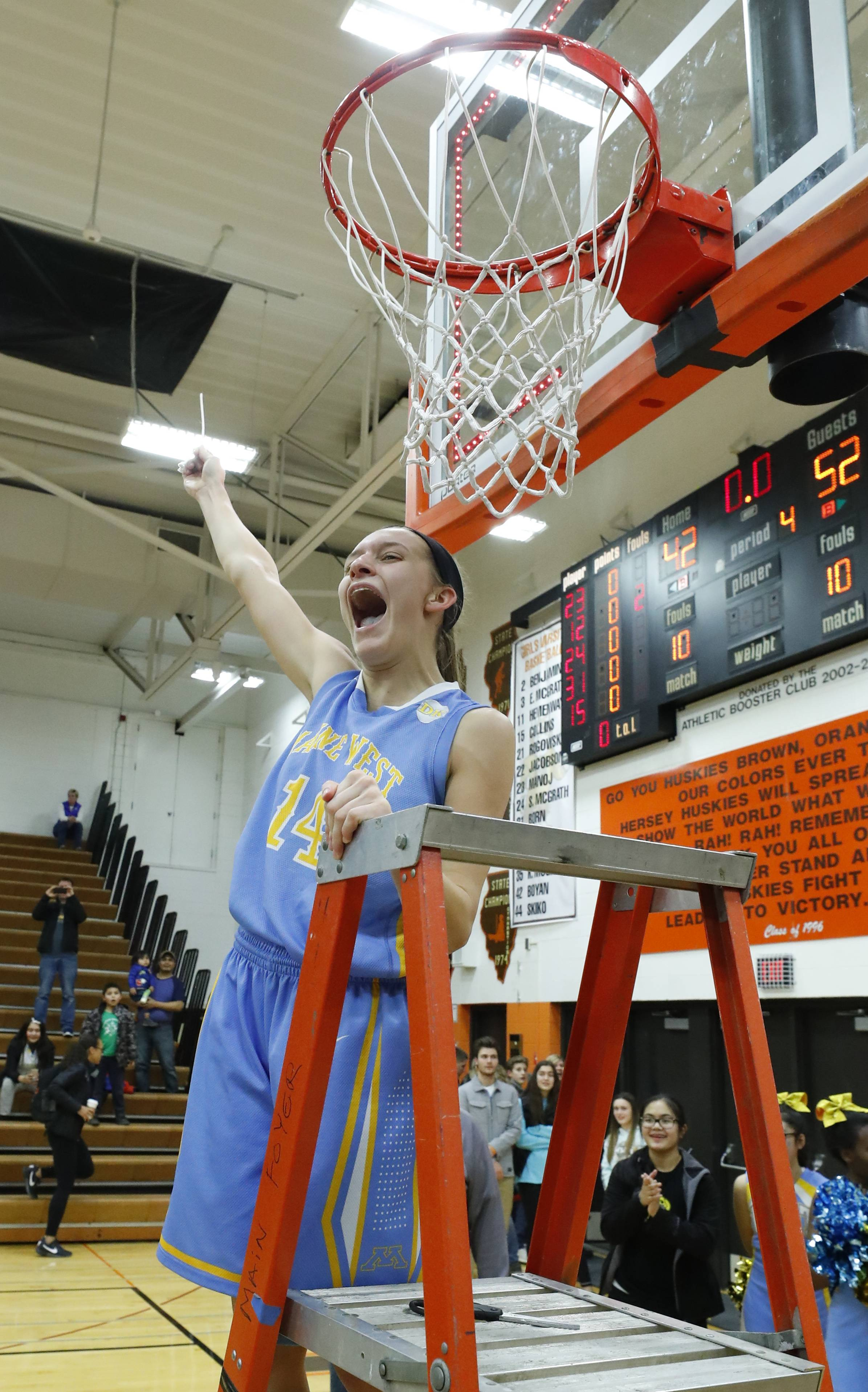 Maine West's Catherine Johnson cuts down the net after the Warriors' 52-42 win over Lake Zurich in the Class 4A Hersey supersectional in Arlington Heights on Monday.