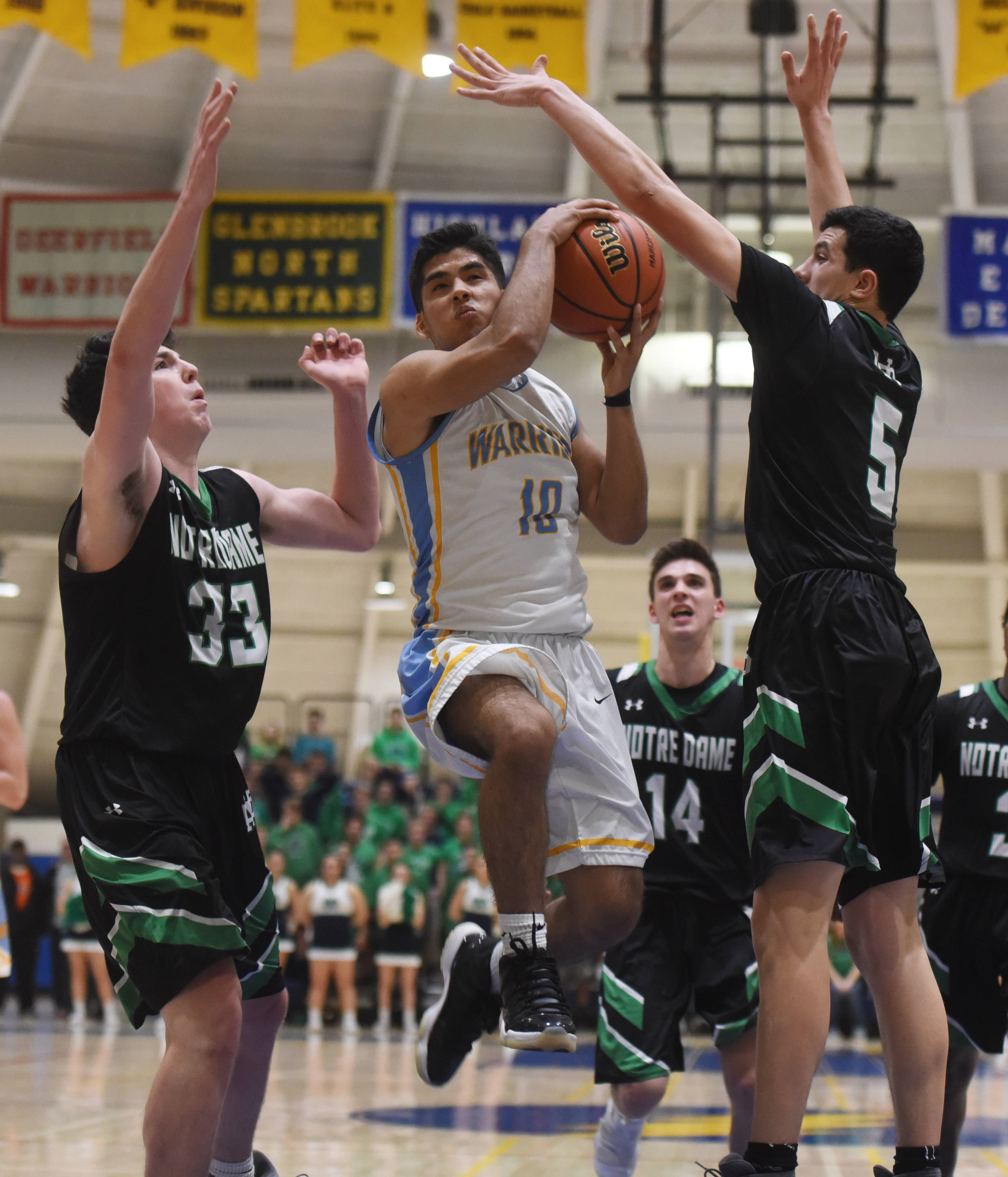 Maine West's Julian Dones drives for a basket between Notre Dame's Troy D'Amico, left, and Jason Bergstrom during the Glenbrook South regional semifinal in Glenview on Tuesday.