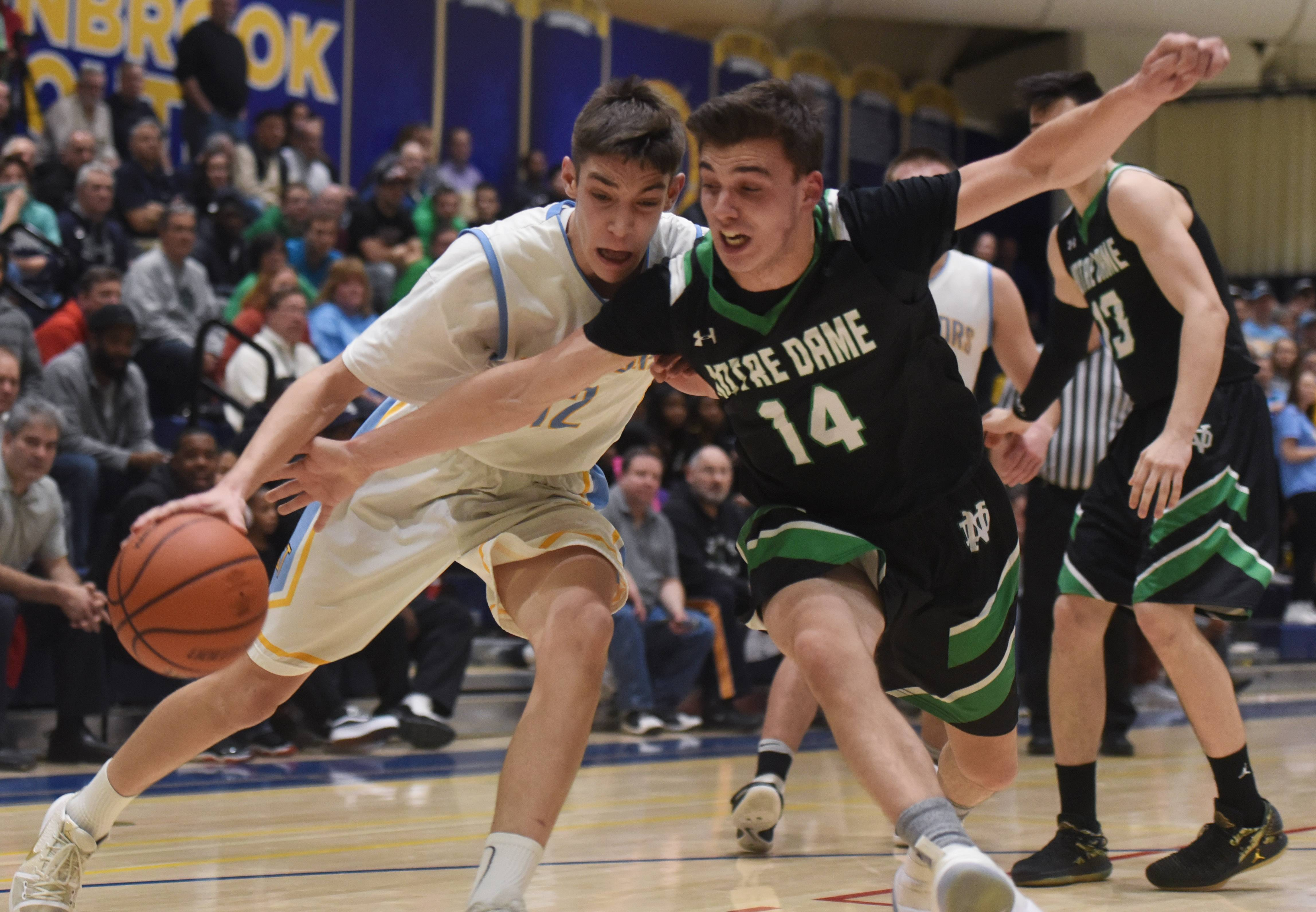 The ball goes off the hand of Maine West's Milos Dugalic and out of bounds as Notre Dame's Adi Tagani defends during the Glenbrook South regional semifinal in Glenview on Tuesday.