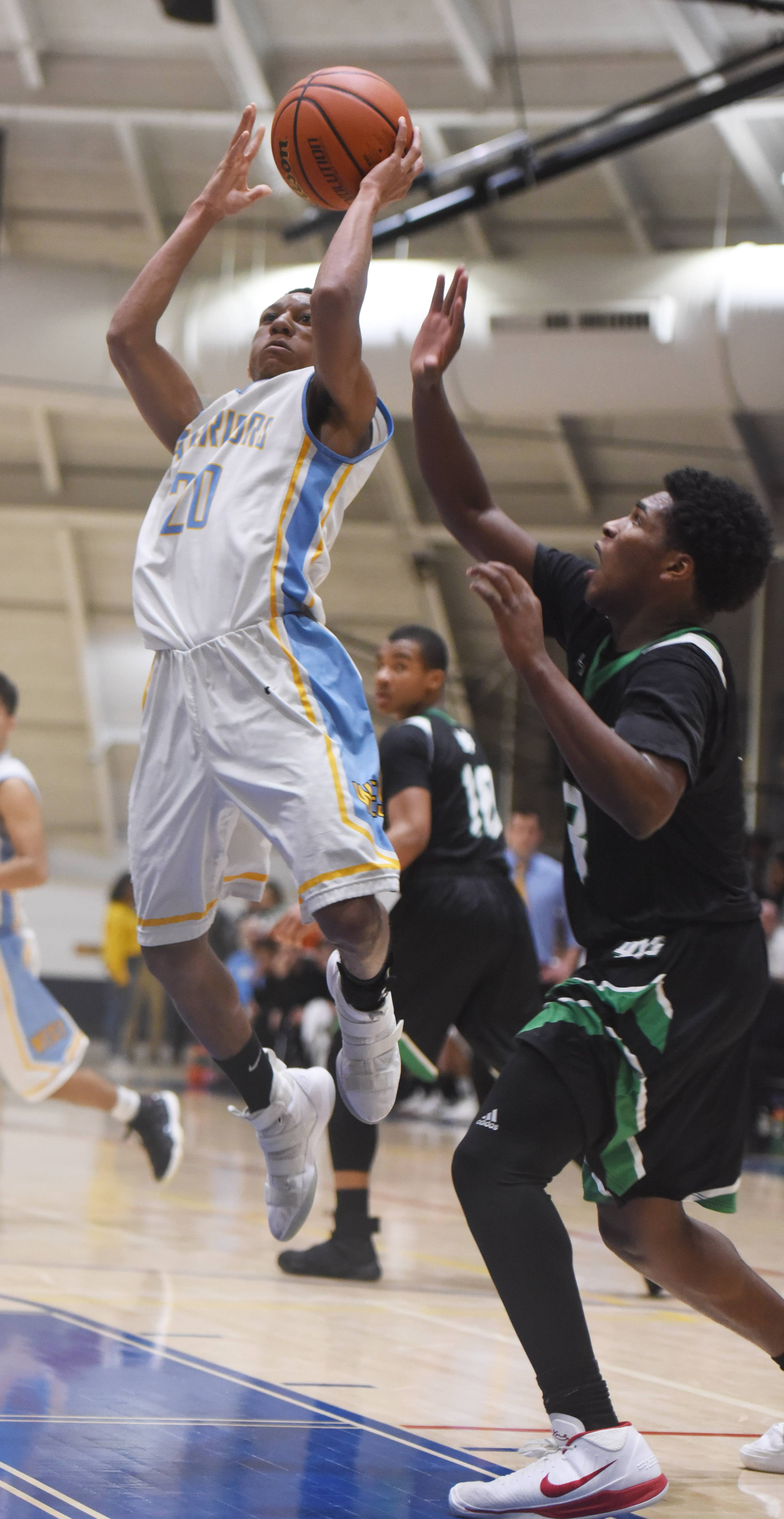 Maine West's Darrington Bates drives to the basket against Notre Dame defender Robert Milam Pryor during the Glenbrook South regional semifinal in Glenview Tuesday.