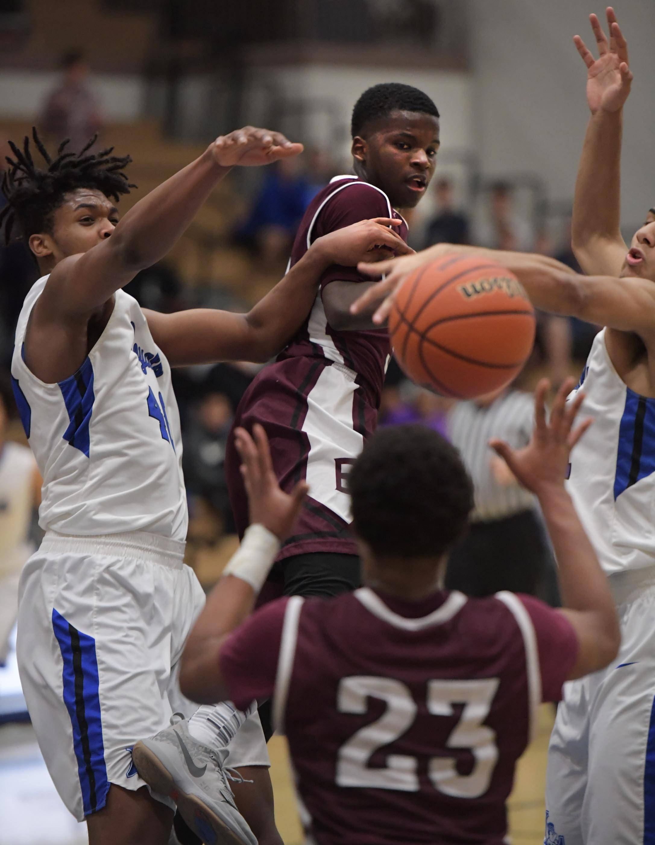 Elgin's Trevon Morris gets a pass to teammate Daz Cooks between the defense of Larkin's Jalen Shaw and Anthony Lynch Tuesday in the St. Charles North boys basketball regional game.