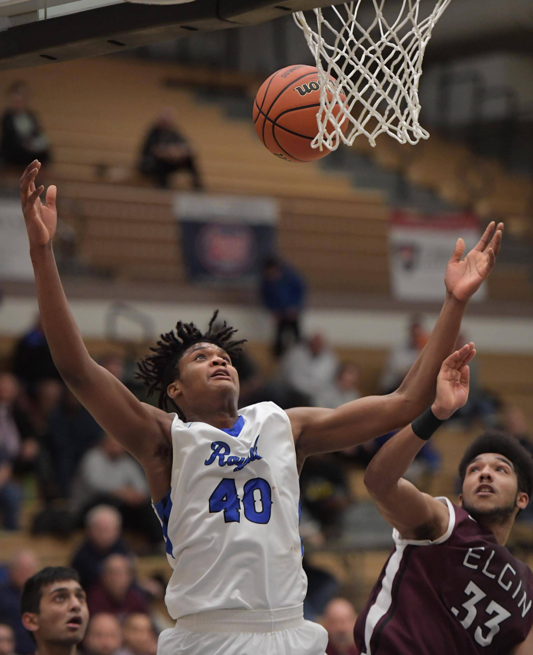 Larkin's Jalen Shaw eyes a rebound against Elgin's Roy Panthier Tuesday in the St. Charles North boys basketball regional game.