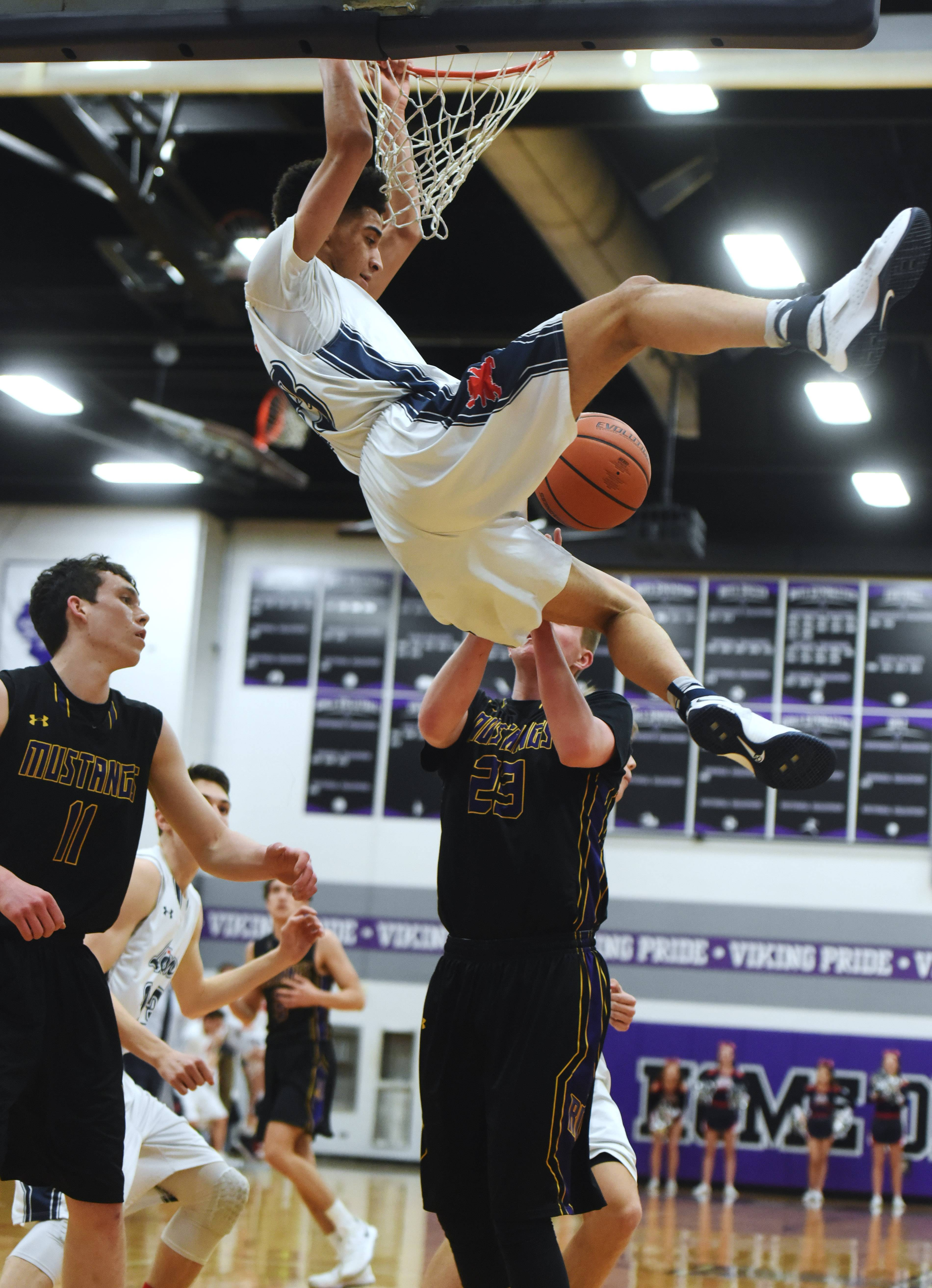 St. Viator's Jeremiah Hernandez dunks in front of Rolling Meadows' Ryan Carney, left, and Joe Coen during regional semifinal play at Niles North in Skokie on Wednesday.