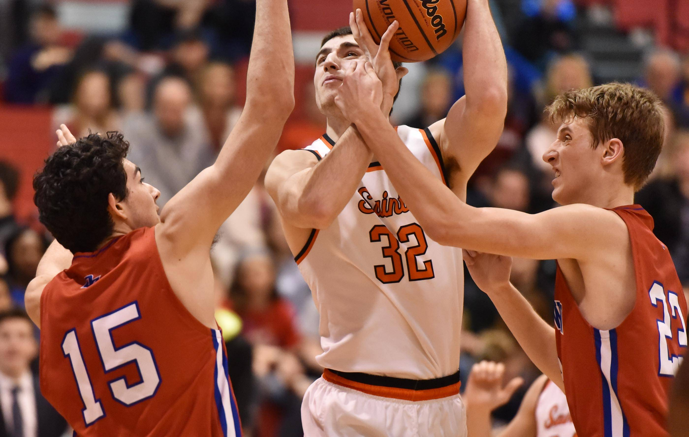 St. Charles East's Justin Hardy is defended by Dundee-Crown's Bradley Stec and Gabriel Bergeron in the Class 4A Dundee-Crown boys basketball semifinal regional game Wednesday.