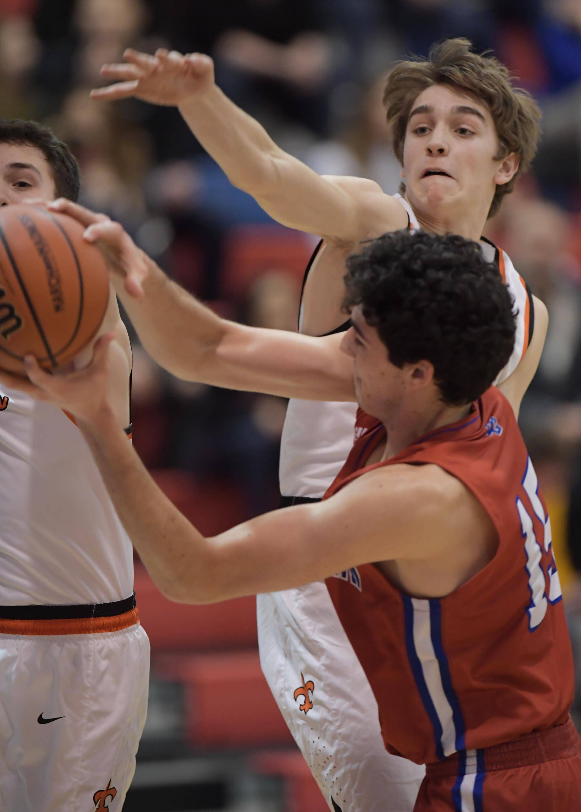 St. Charles East's Mark Musial disrupts the play of Dundee-Crown's Gabriel Bergeron in the Class 4A Dundee-Crown boys basketball semifinal regional game Wednesday.