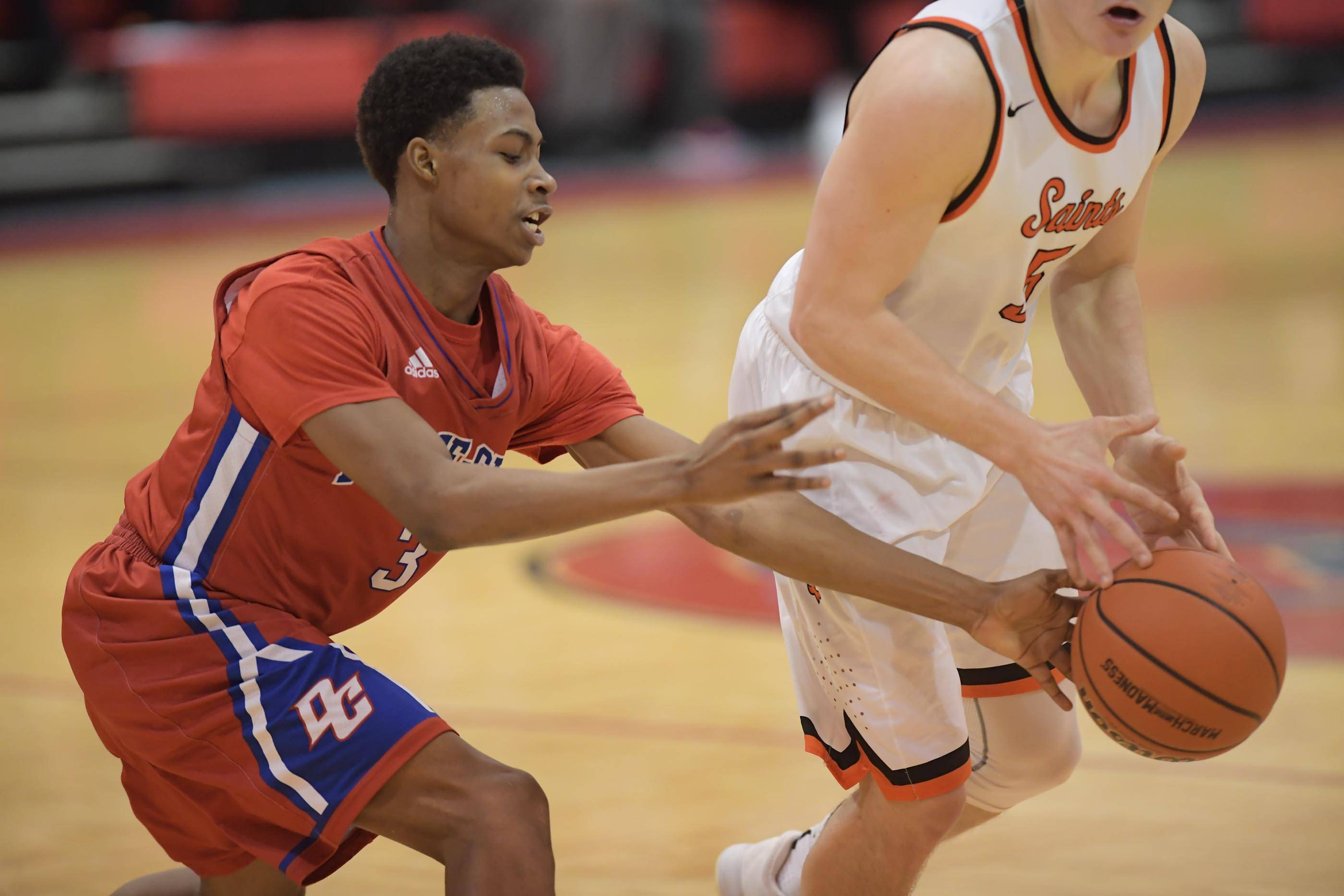 Dundee-Crown's Damarion Butler swats the ball from St. Charles East's Zachary Robinson in the Class 4A Dundee-Crown boys basketball semifinal regional game Wednesday.