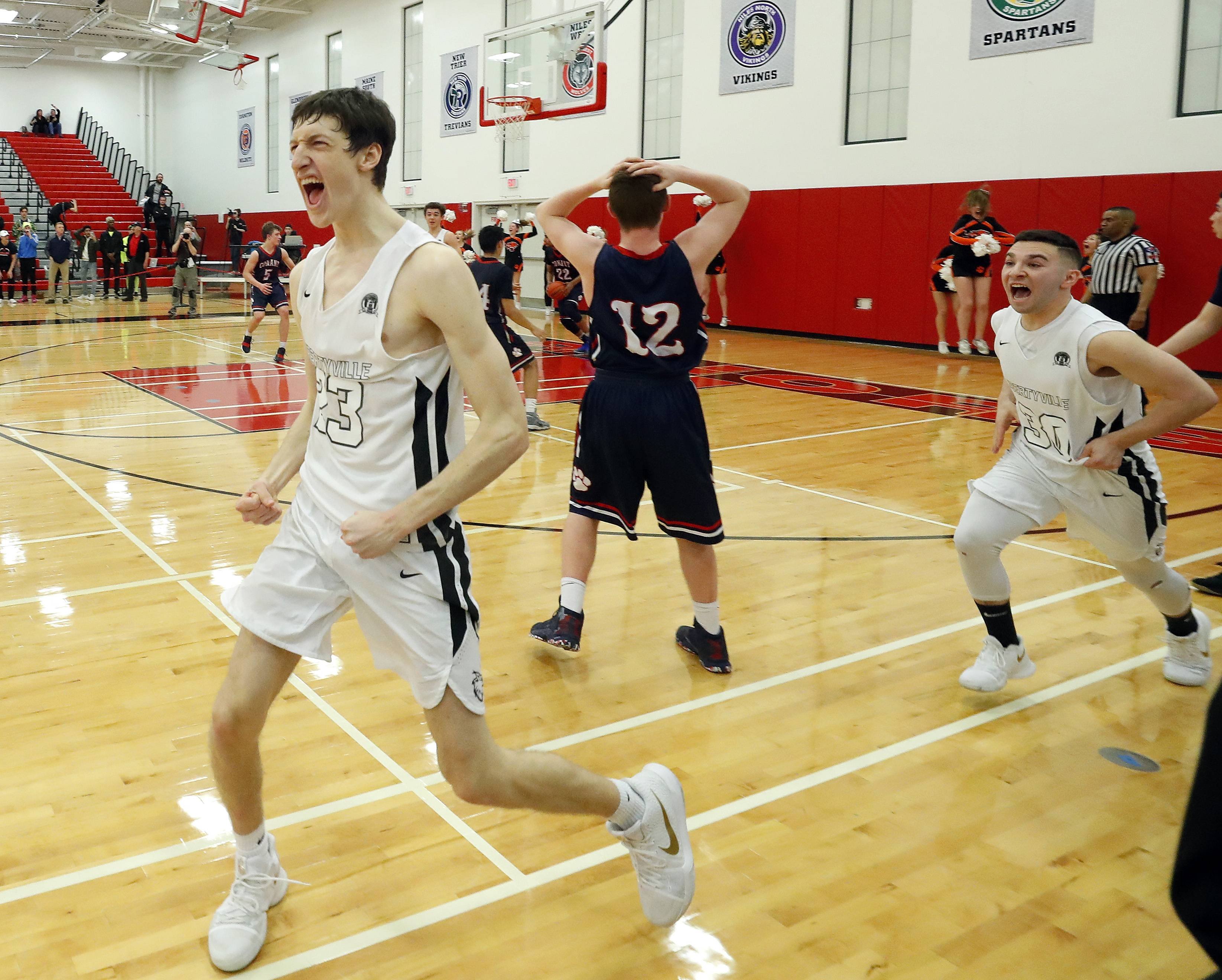 Libertyville's Drew Peterson, left, reacts after hitting a buzzer beater to finish a 59-56 win over Conant in Class 4A regional final play Friday night at Deerfield High School.