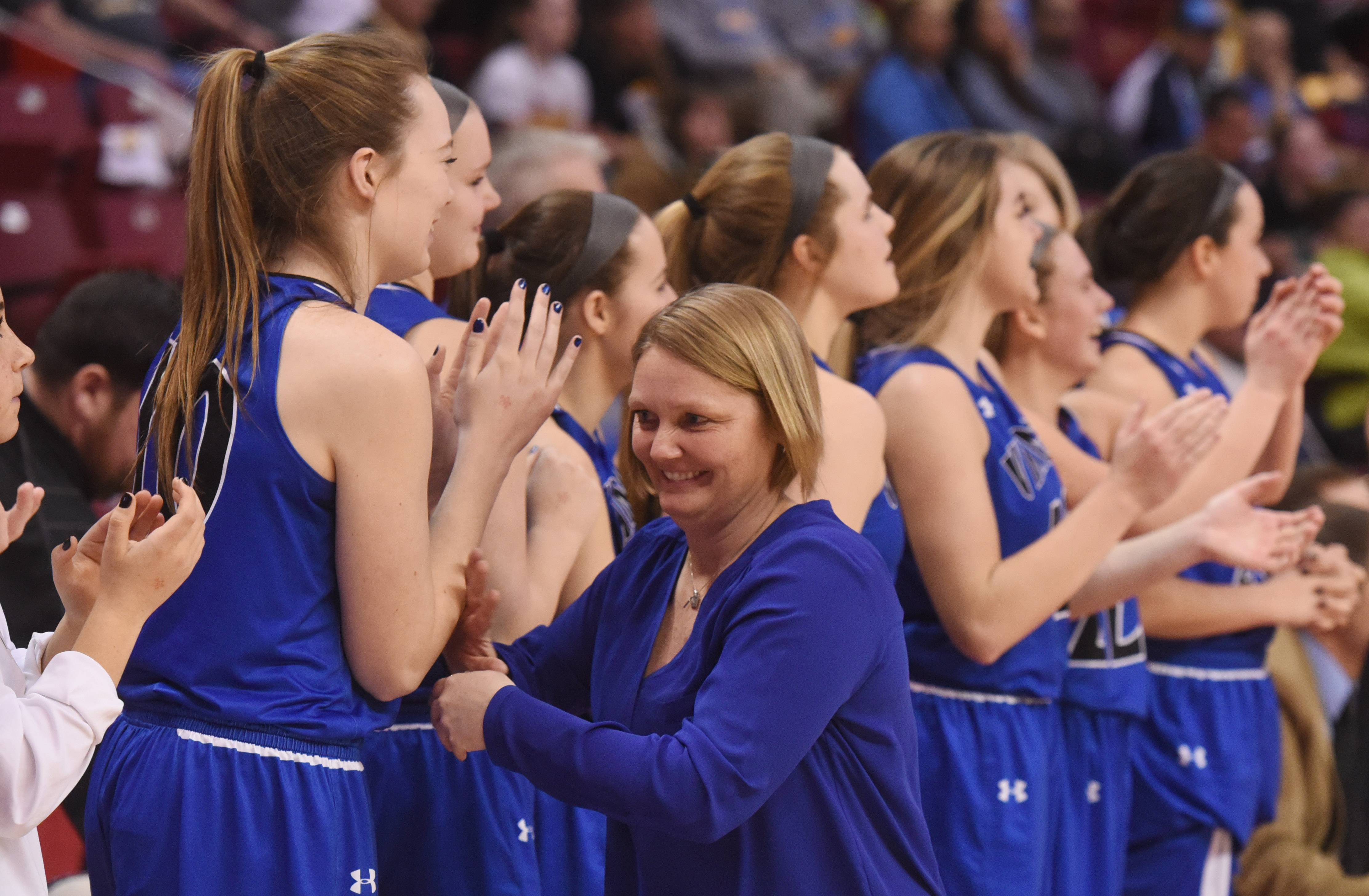 Geneva head coach Sarah Meadows celebrates with her team members at the conclusion of the Vikings' 58-41 win over Maine West during the Class 4A girls basketball semifinals at Redbird Arena in Normal Friday.