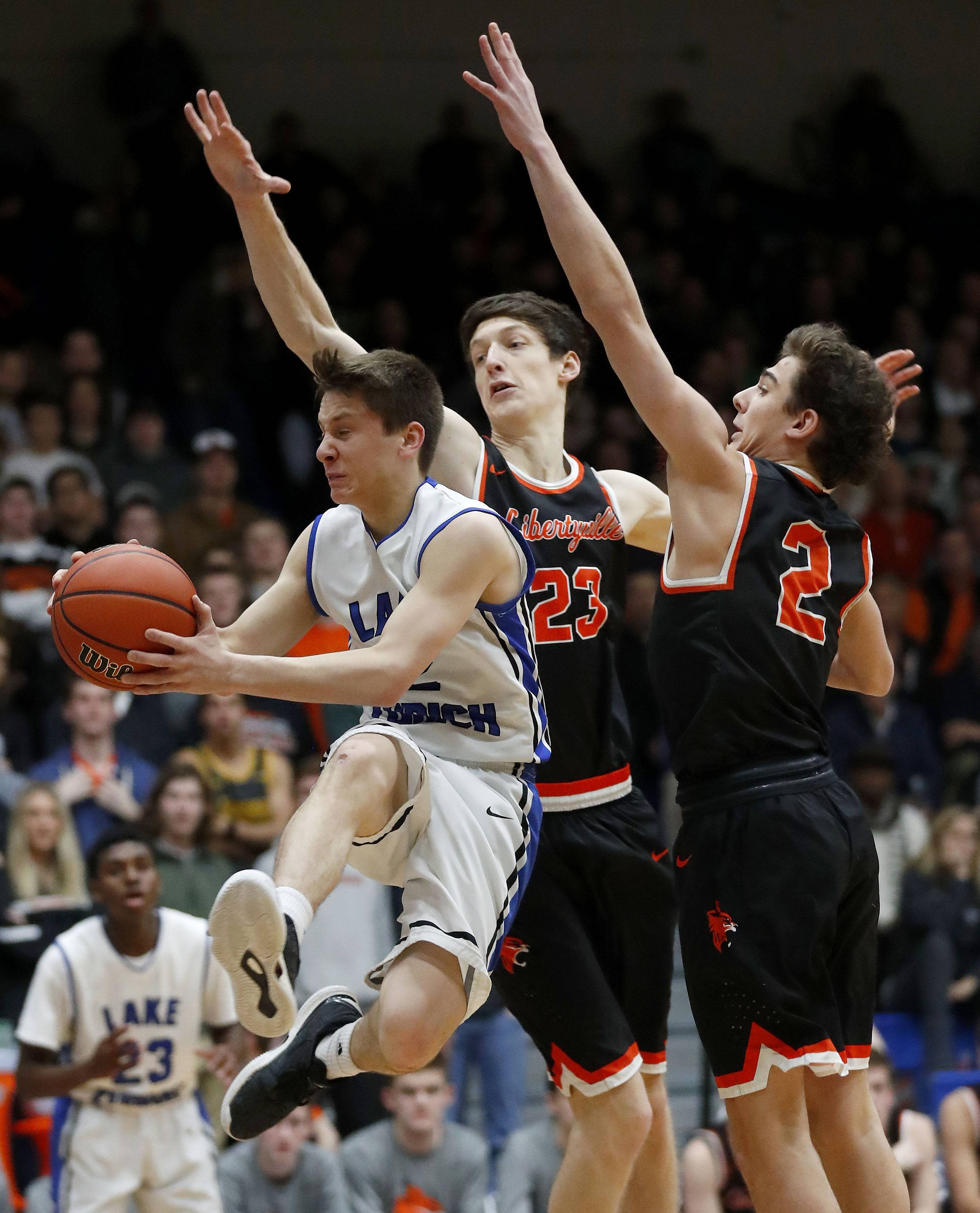 Lake Zurich's JR Cison, left, drives on Libertyville's Drew Peterson and Brian Wilterdink during the Class 4A sectional semifinal at Lake Zurich High School on Tuesday.