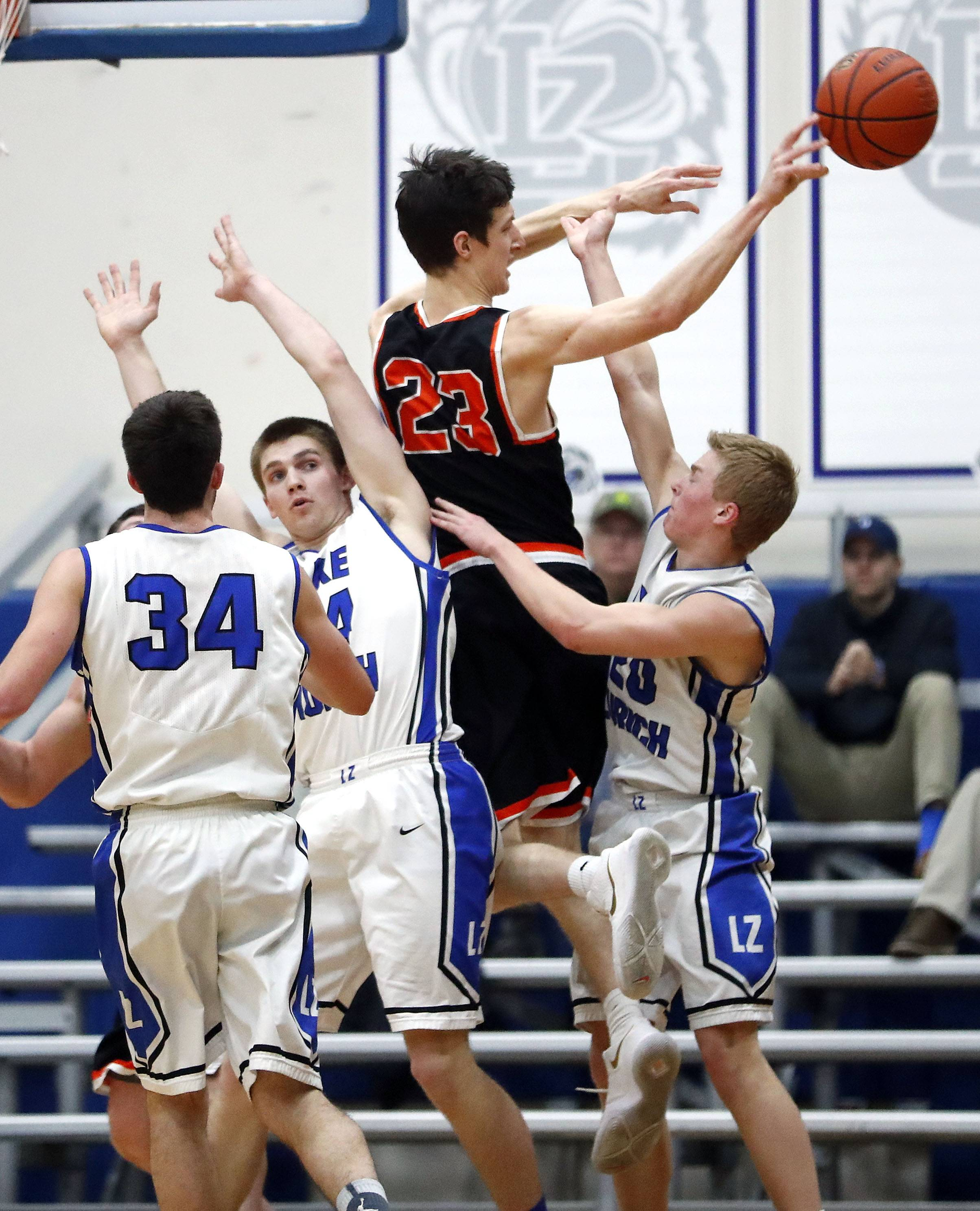 Libertyville's Drew Peterson dishes off around Lake Zurich's Ryan Kutsor and Joe Heffernan during the Class 4A sectional semifinal at Lake Zurich High School on Tuesday.