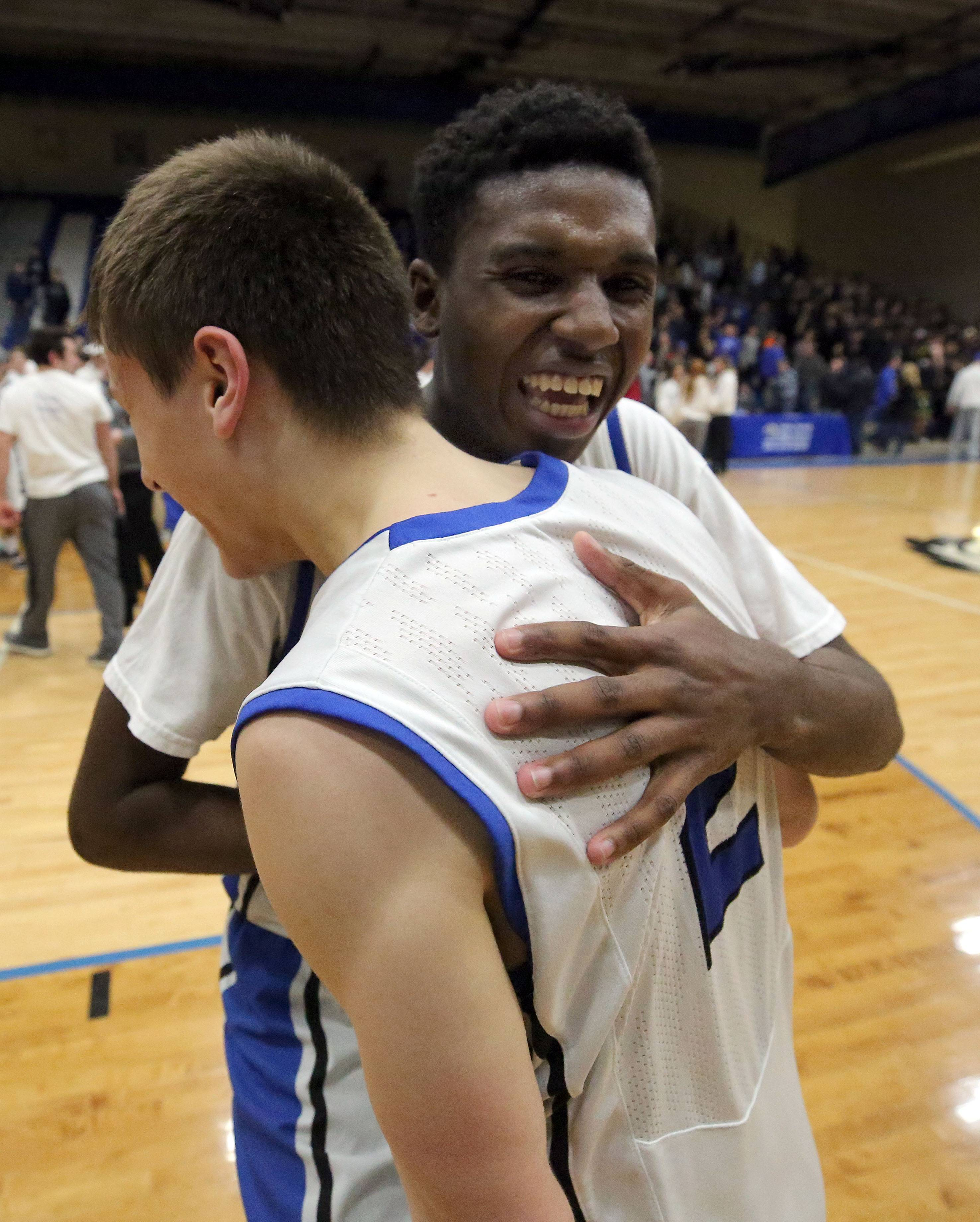 Lake Zurich's Kenny Haynes, right, hugs teammate JR Cison during the Class 4A sectional semifinal at Lake Zurich High School on Tuesday. The Bears topped Libertyville 54-50 to earn a spot in Friday's final; see story on Page 6.