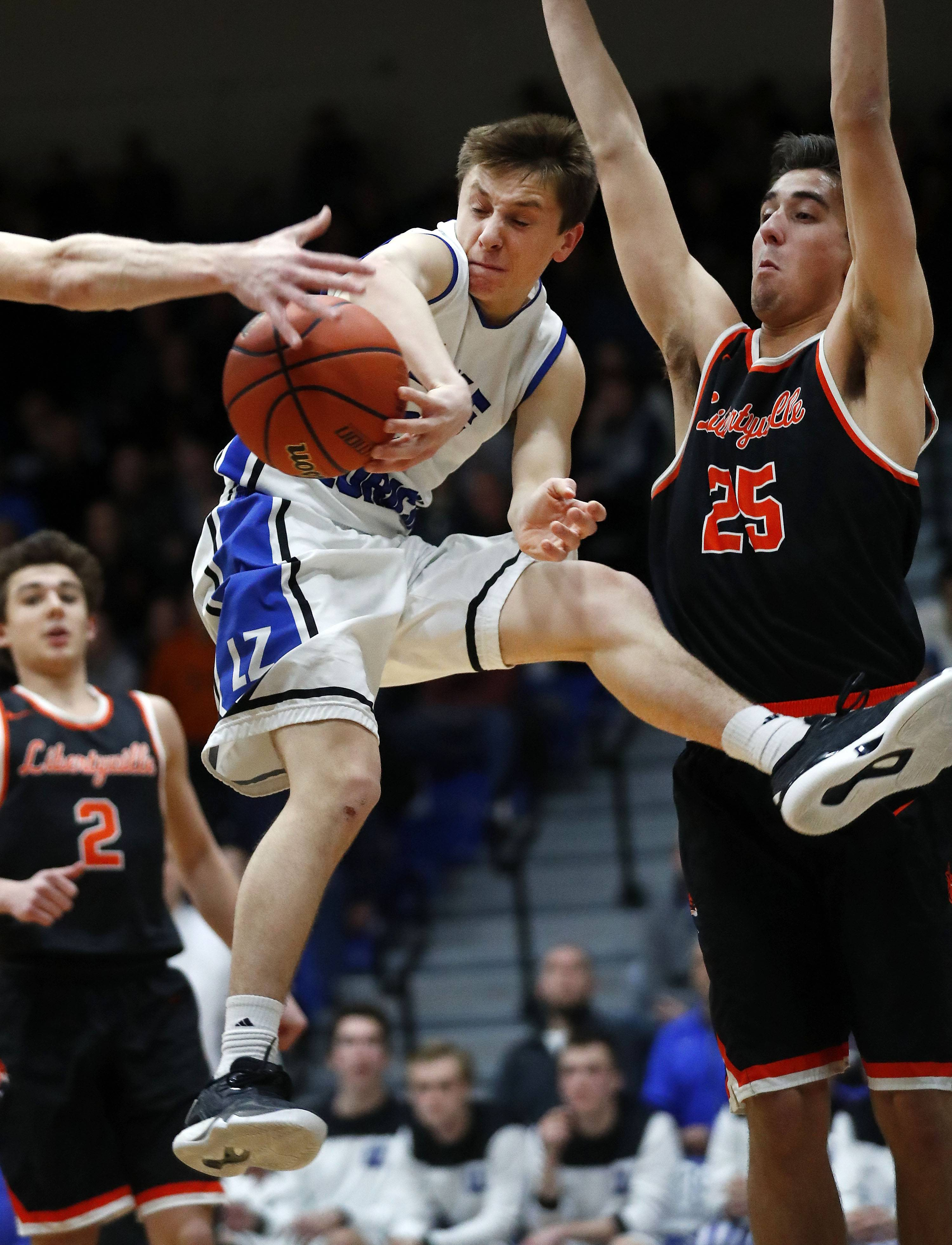 Lake Zurich's JR Cison dishes off as Libertyville's Chase Eyre defends during the Class 4A sectional semifinal at Lake Zurich High School on Tuesday.