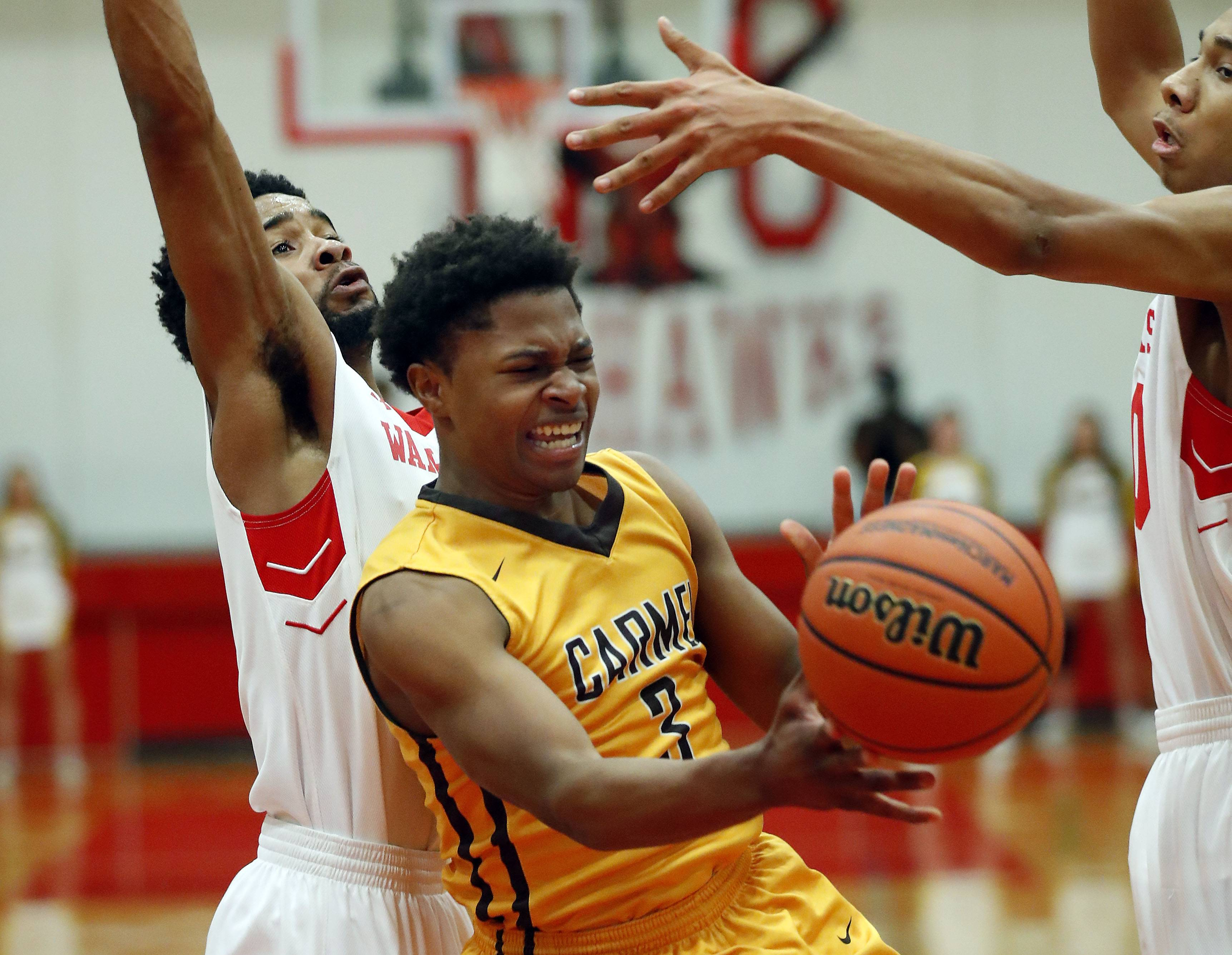 Carmel's Zion Kilpatrick (3) drives on North Chicago's Ishaun Walker during Class 3A sectional semifinal play Wednesday at North Chicago.