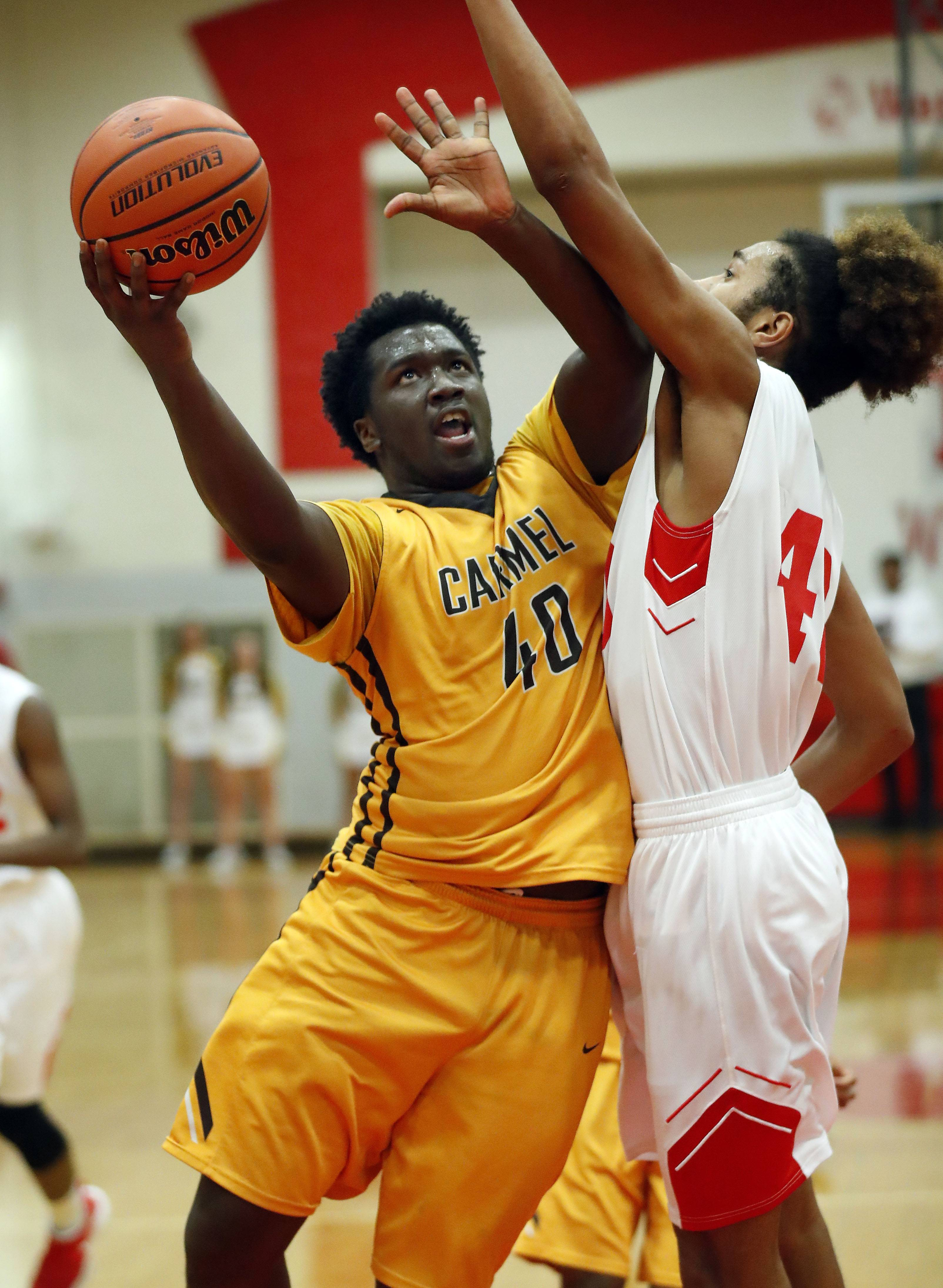 Carmel's Jalen Snell (40) drives on North Chicago's Raeshaun Samoa during Class 3A sectional semifinal play Wednesday at North Chicago.