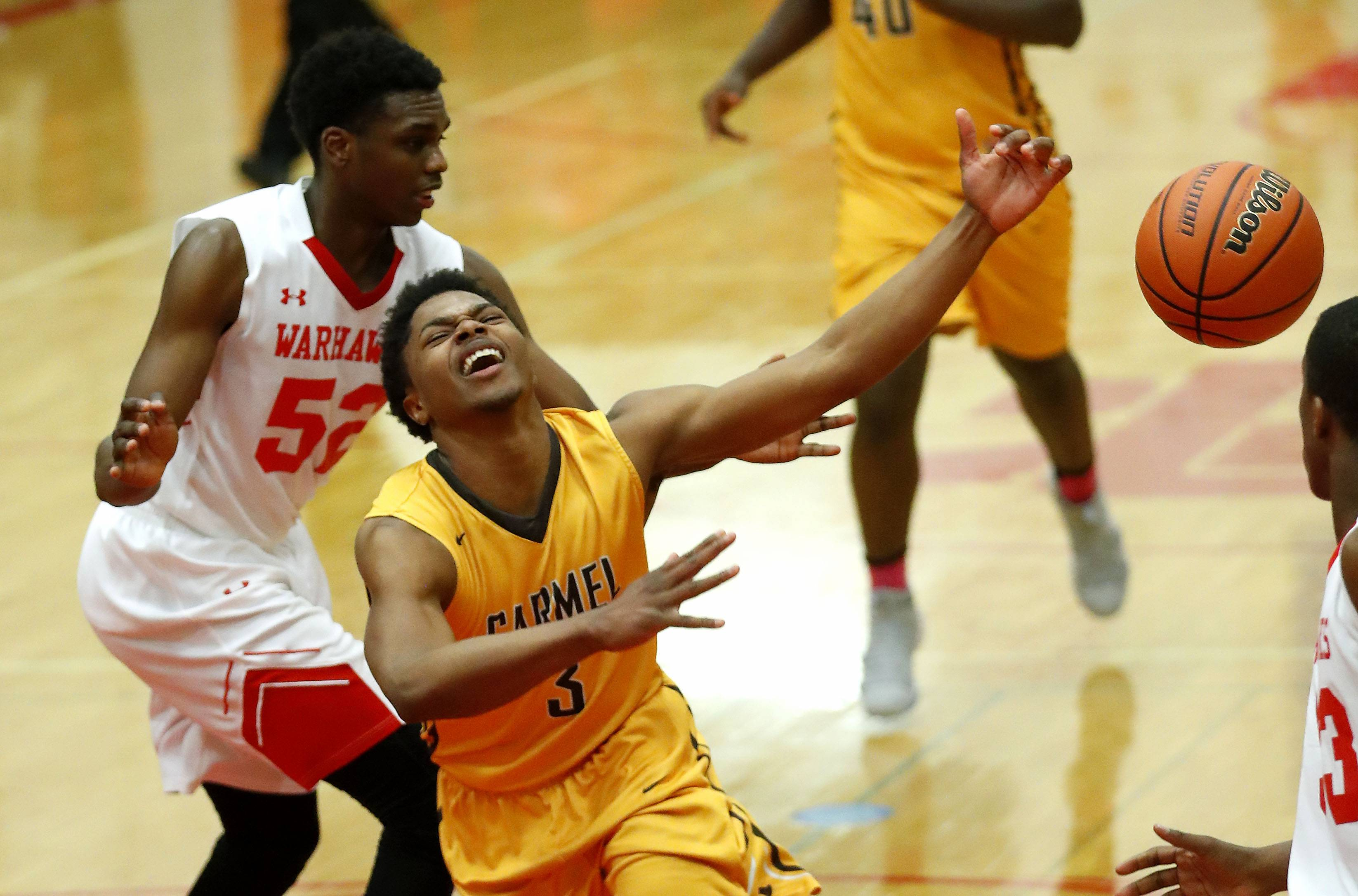 Carmel's Zion Kilpatrick is fouled by North Chicago's Pierce Coleman during Class 3A sectional semifinal play Wednesday at North Chicago.