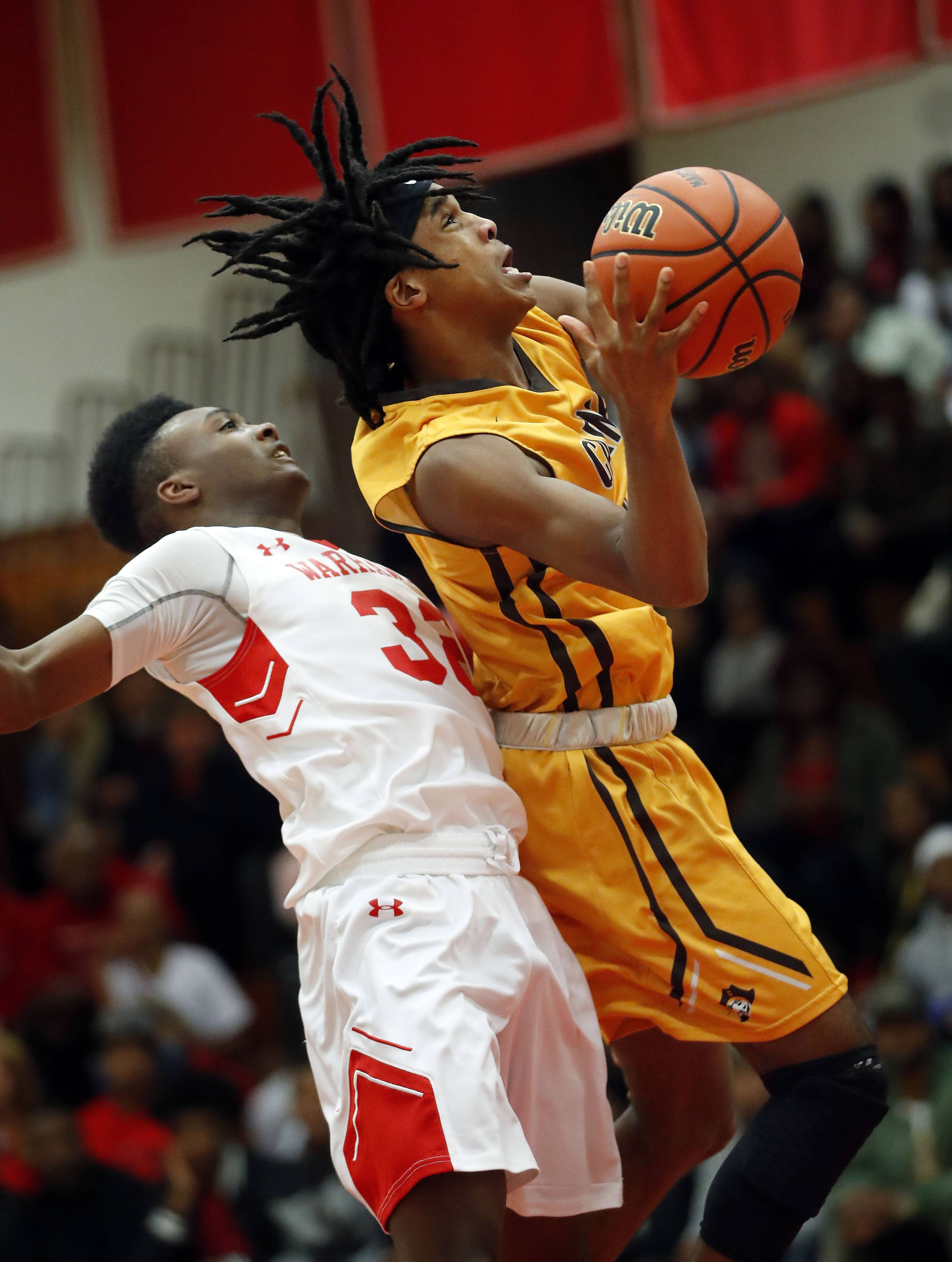 Carmel's Kimahri Wilson, right, drives on North Chicago's DyShawn Gales during Class 3A sectional semifinal play Wednesday at North Chicago.