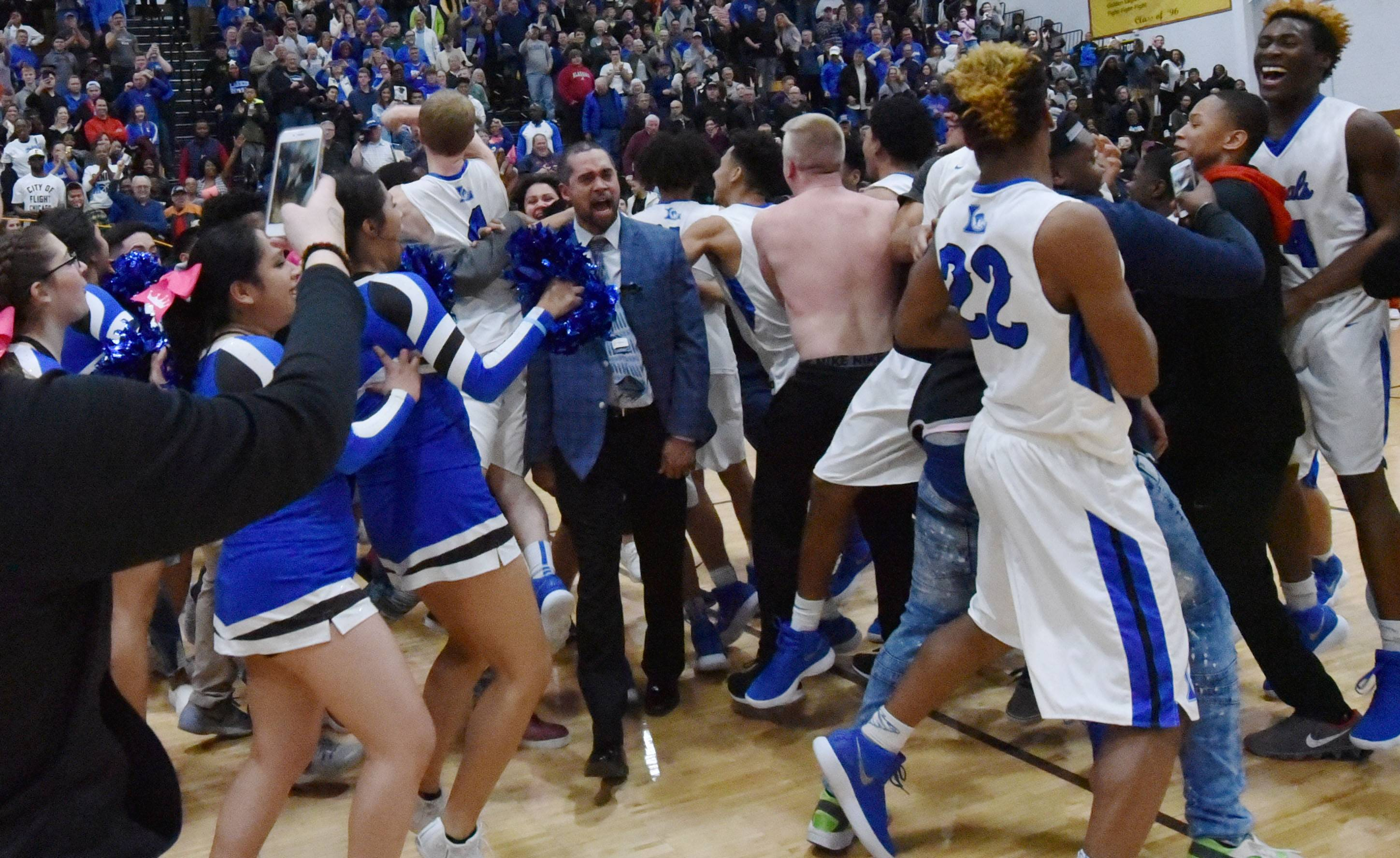 Larkin head basketball coach Deryn Carter celebrates with his team after defeating Rockford Jefferson in the Class 4A Jacobs sectional championship boys basketball game in Algonquin Friday.
