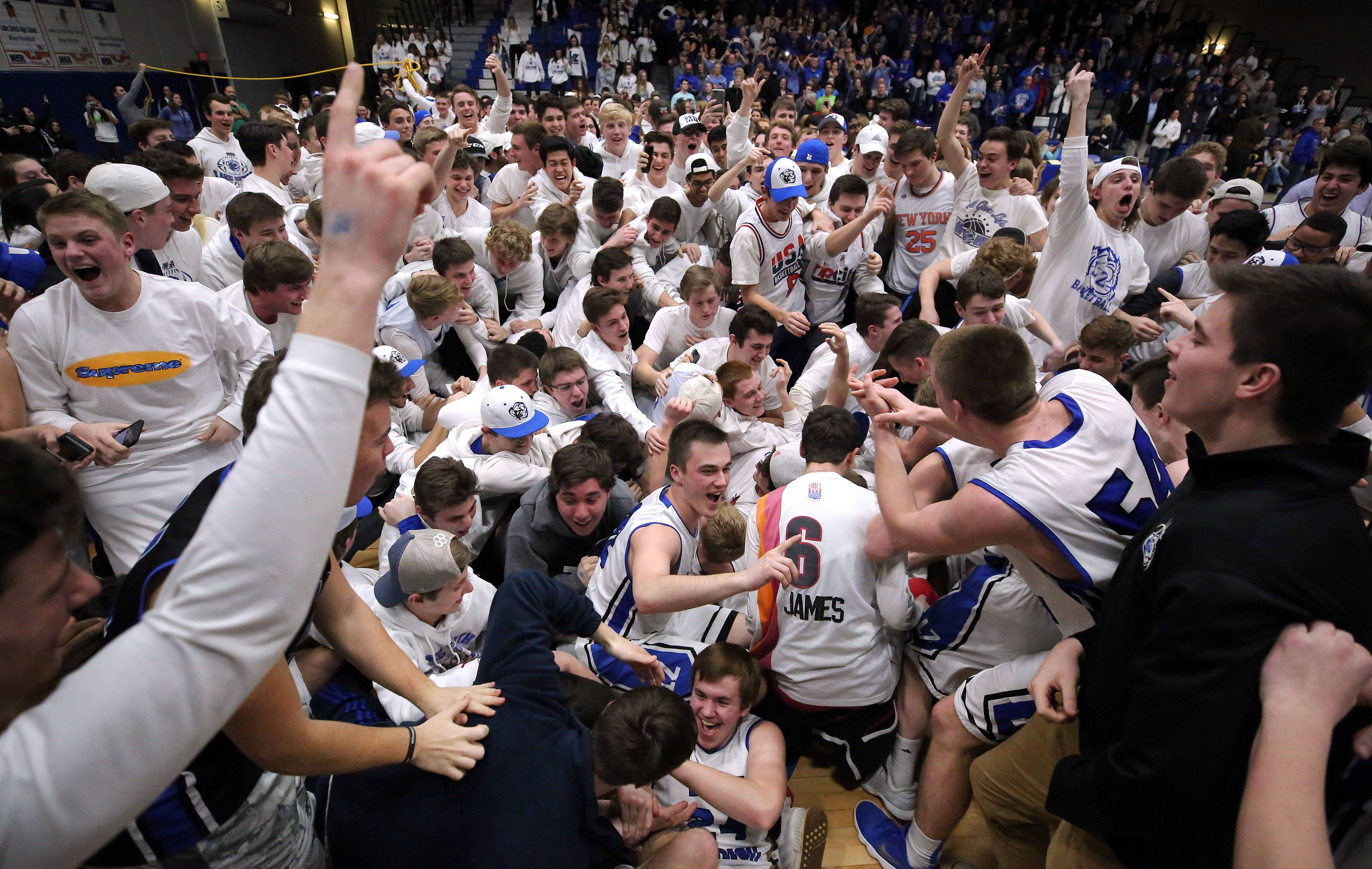 Fans mob the Lake Zurich players after a 69-60 win over Barrington in the Class 4A sectional final at Lake Zurich on Friday.