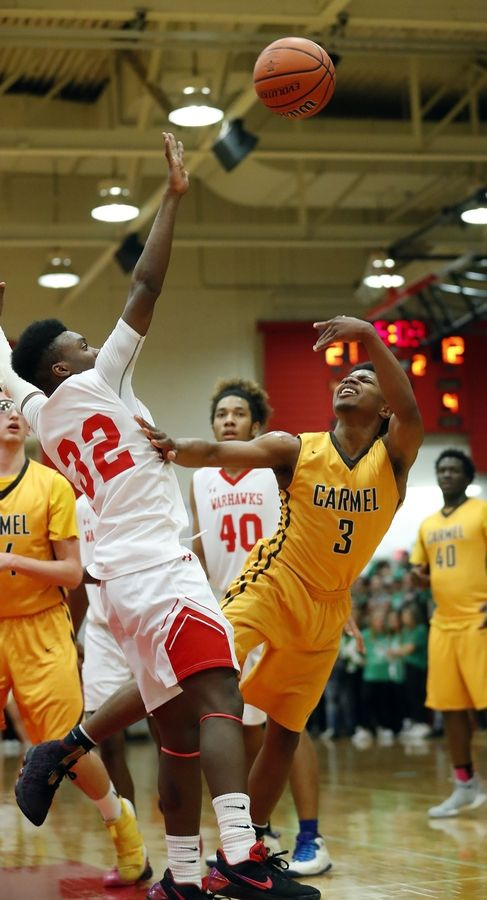 North Chicago's DyShawn Gales defends as Carmel's Zion Kilpatrick tries to lift a shot over him during Class 3A sectional semifinal play at North Chicago.