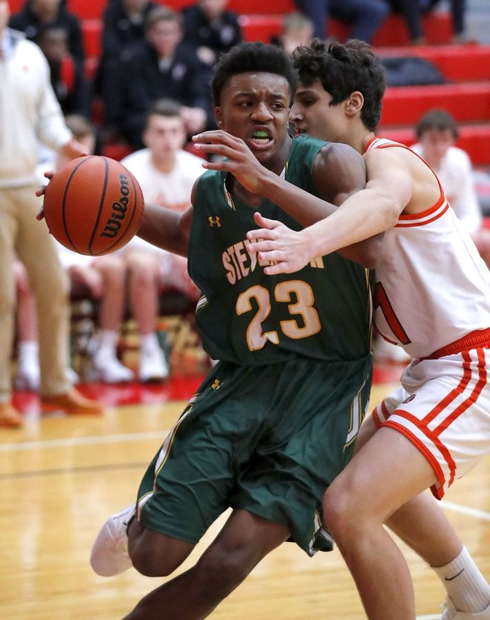 Stevenson's RJ Holmes (23) drives on Hersey's Jason Coffaro during their game Tuesday at Palatine High School.