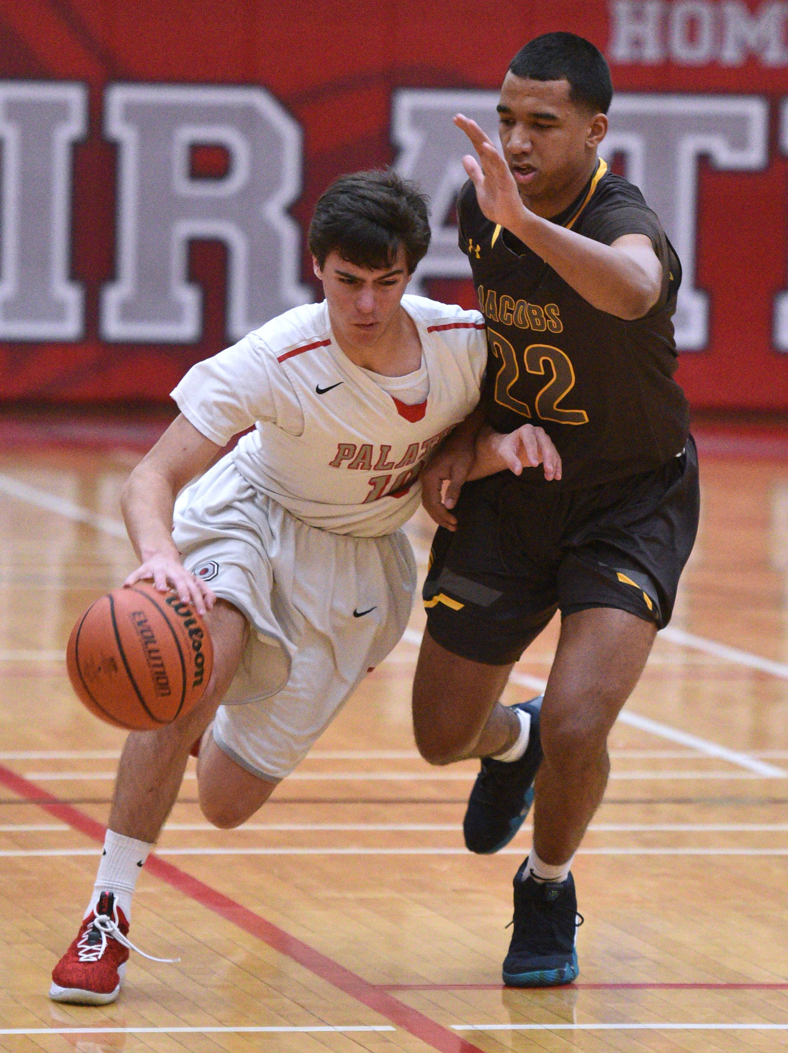 Palatine's Luke Seiffert, left, drives past Jacobs' Jaden Henderson (22) during the boys basketball game Friday in Palatine.