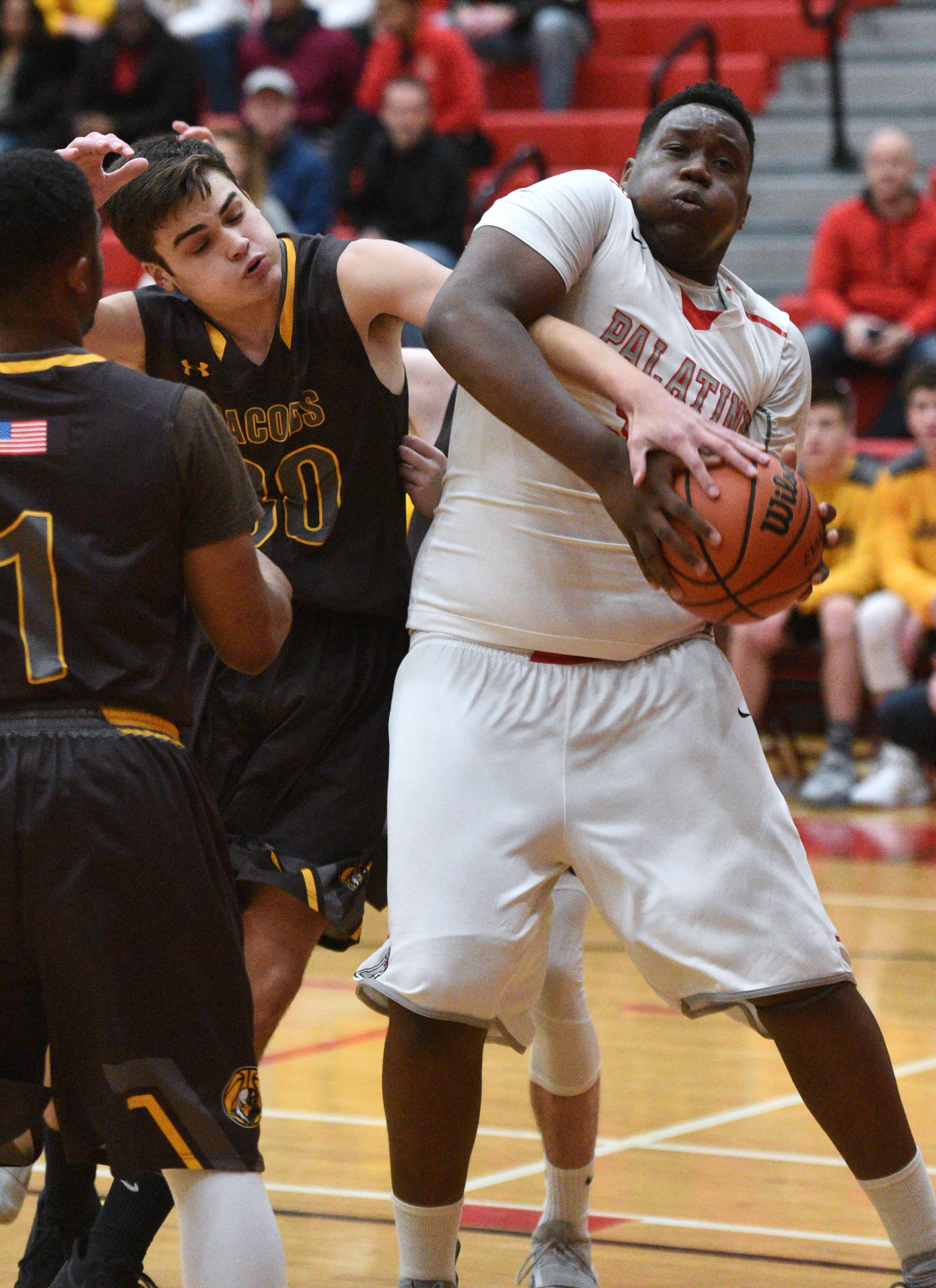 Jacobs' Riley Anderson, left, and Palatine's Julian Campbell fight for a rebound during Friday's boys basketball game in Palatine.