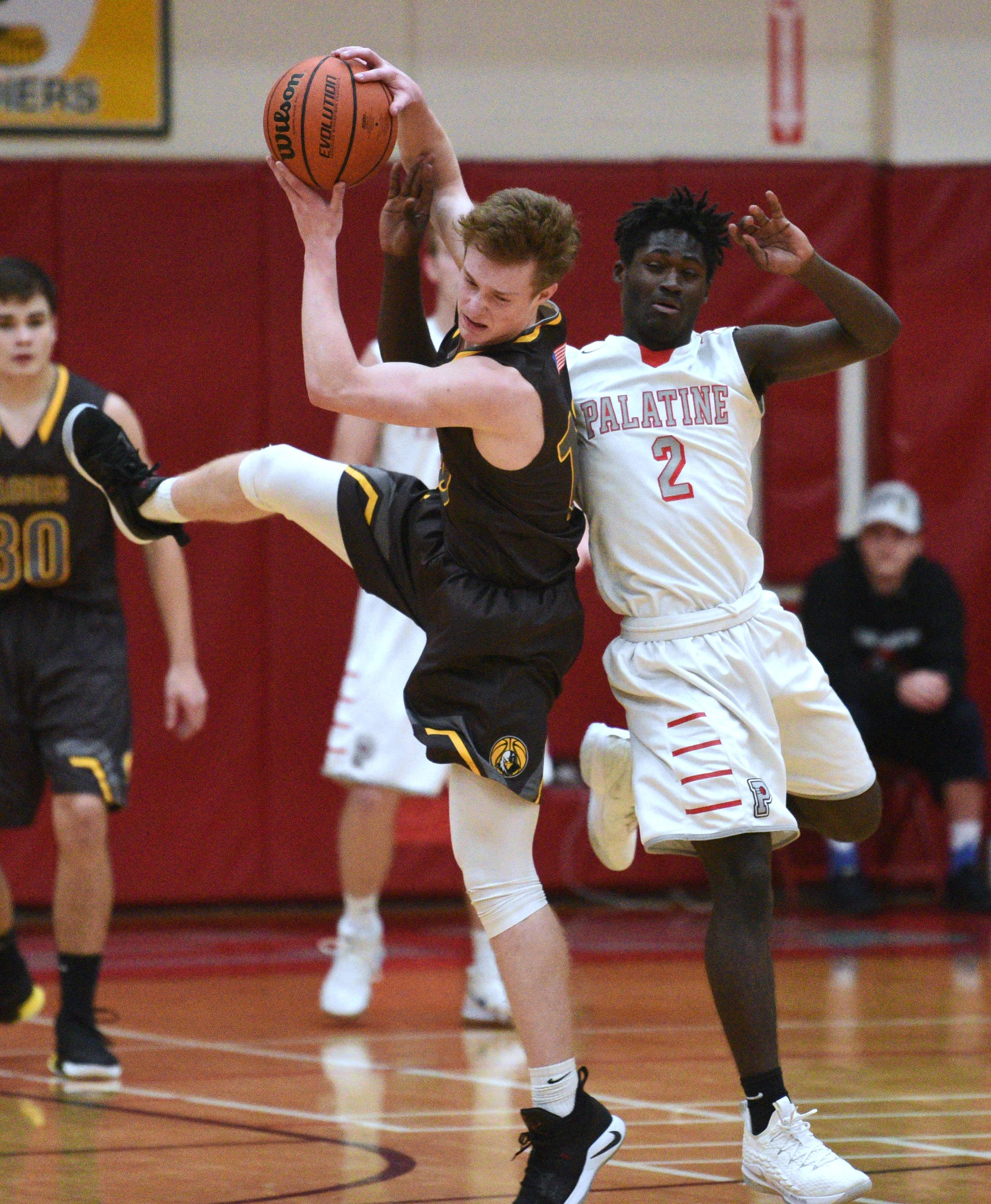 Jacobs' Matt McCoy, left, pulls down a pass under pressure from Palatine's Marshawn Rayford (2) during Friday's boys basketball game in Palatine.
