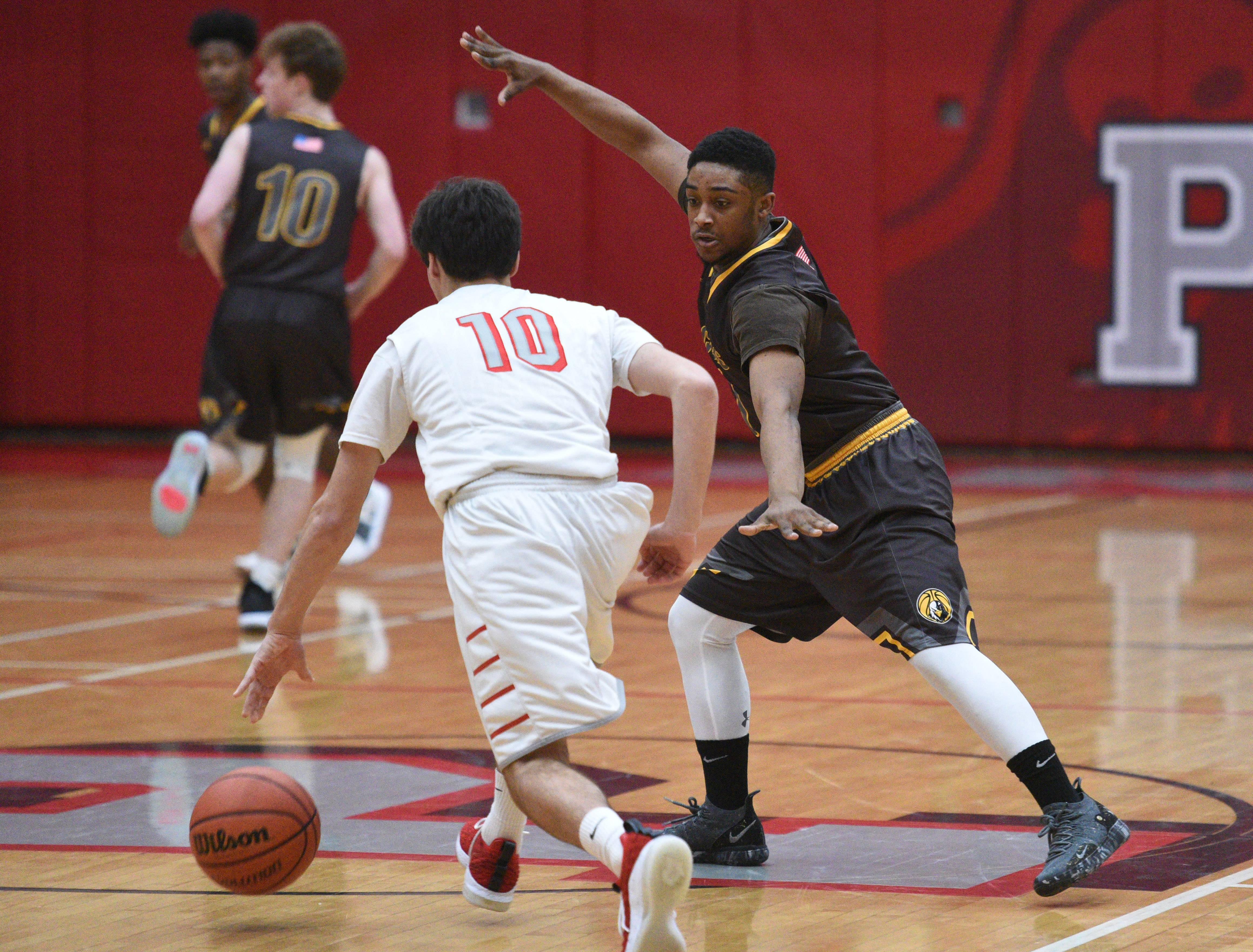 Jacobs' Jalen Ramsey, right, pressures Palatine's Luke Seiffert (10) during the boys basketball game Friday in Palatine.