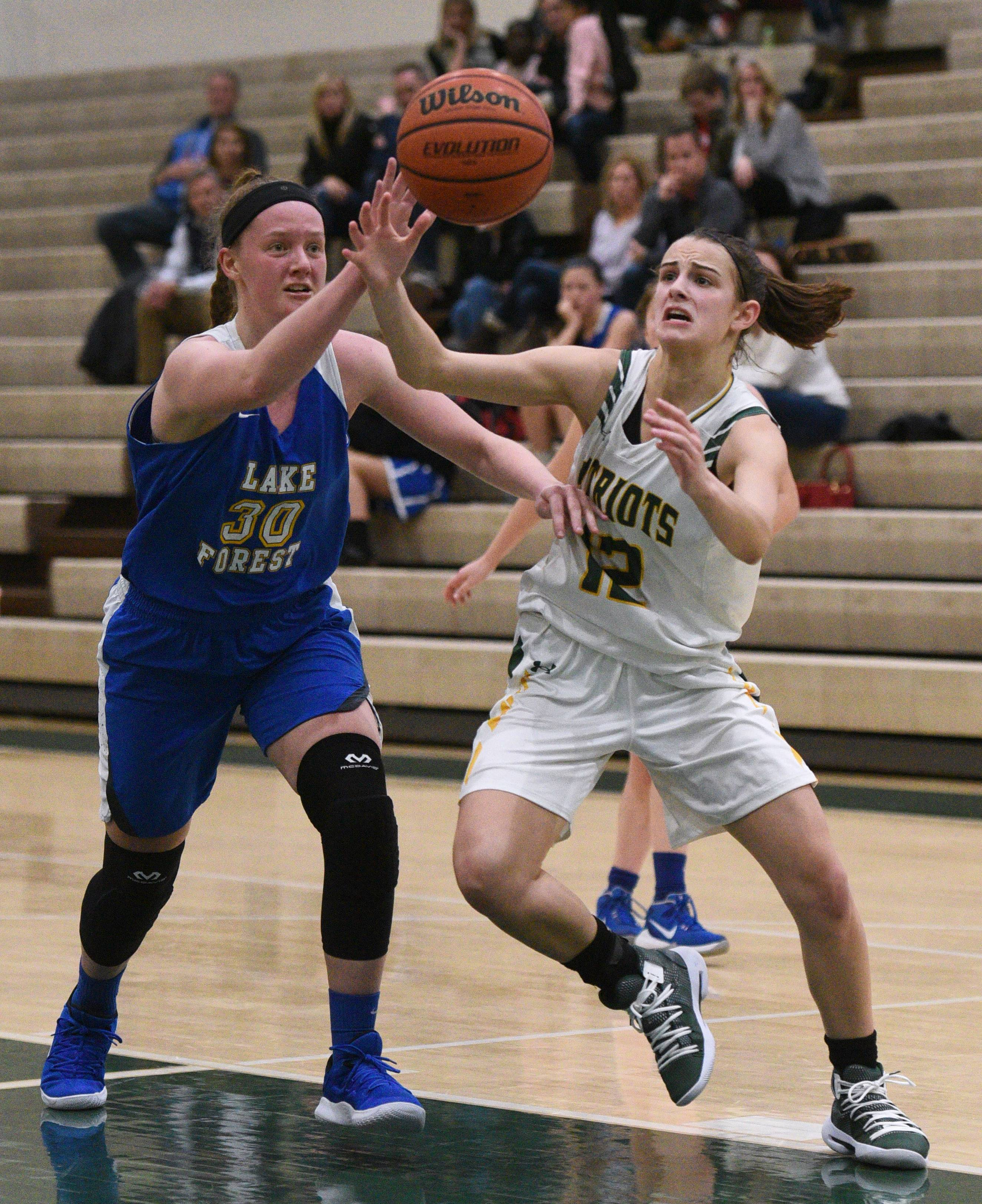 Stevenson's Krissy Hill (12) scrambles for the ball with Lake Forest's Ellie Pearson (30) during Friday's girls basketball game in Lincolnshire.