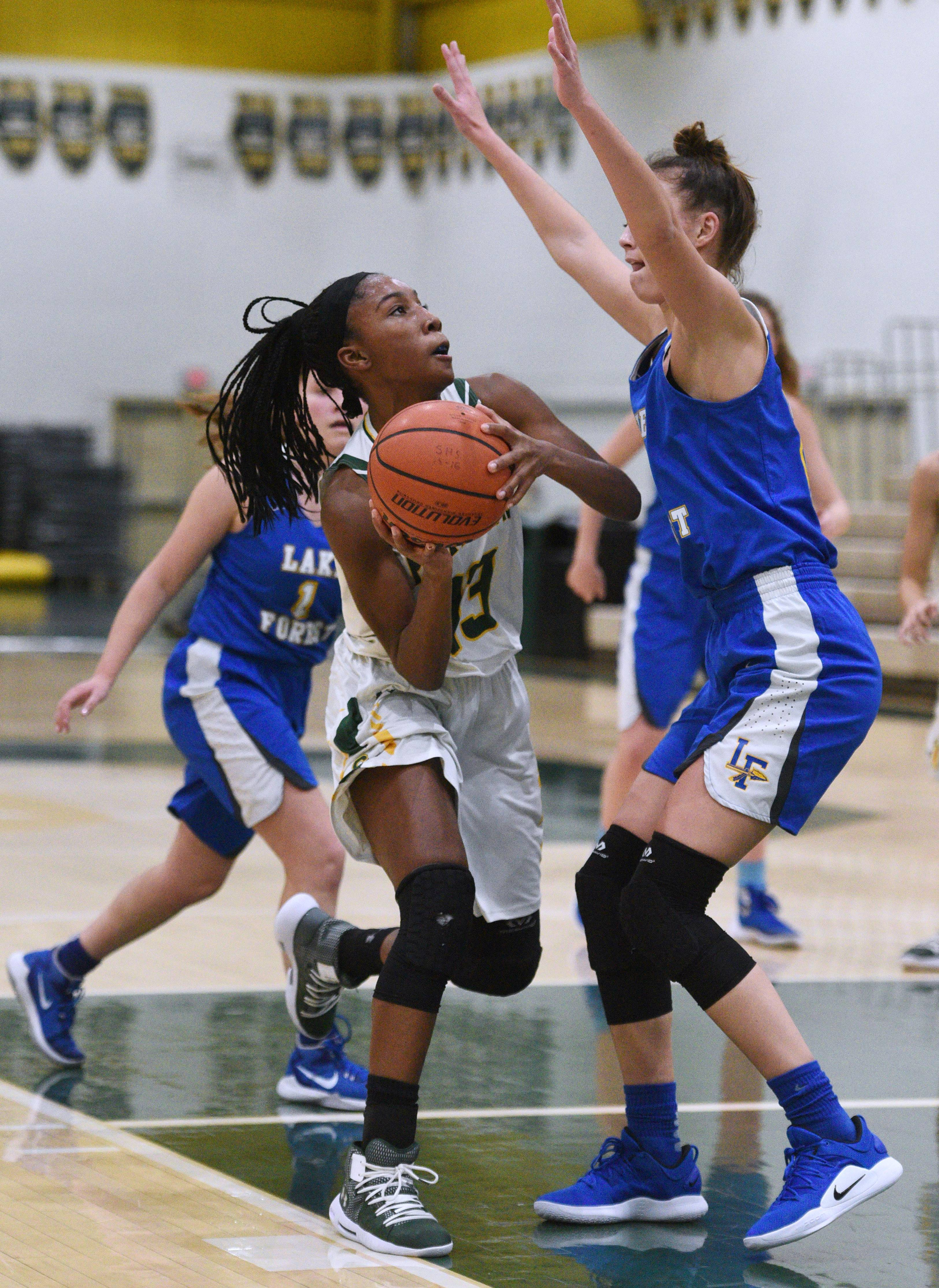 Stevenson's Simone Sawyer (13) looks for a shot over Lake Forest's Halle Douglass during Friday's girls basketball game in Lincolnshire.