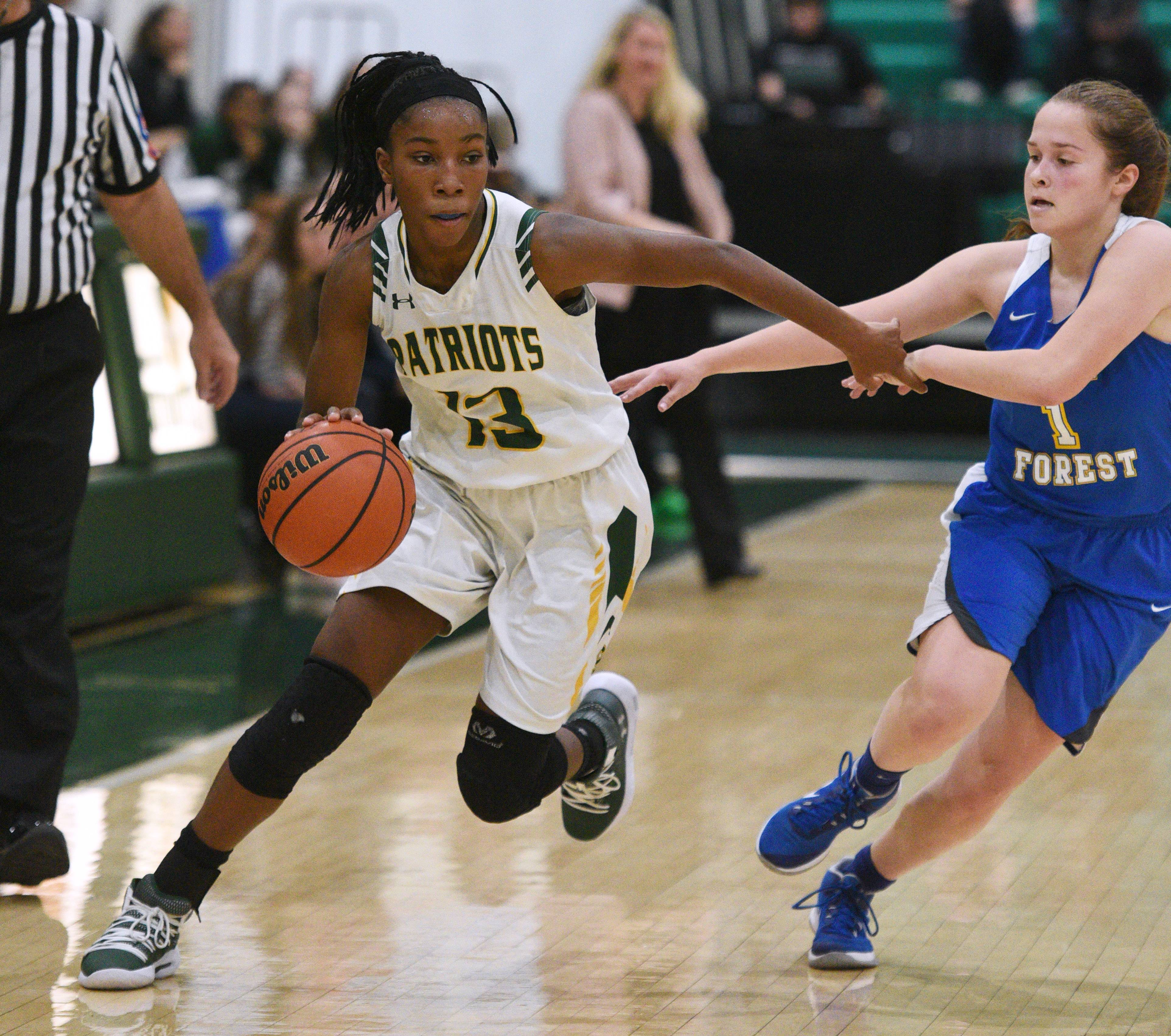 Stevenson's Simone Sawyer (13) drives past Lake Forest's Molly Fisher (1) during Friday's girls basketball game in Lincolnshire.