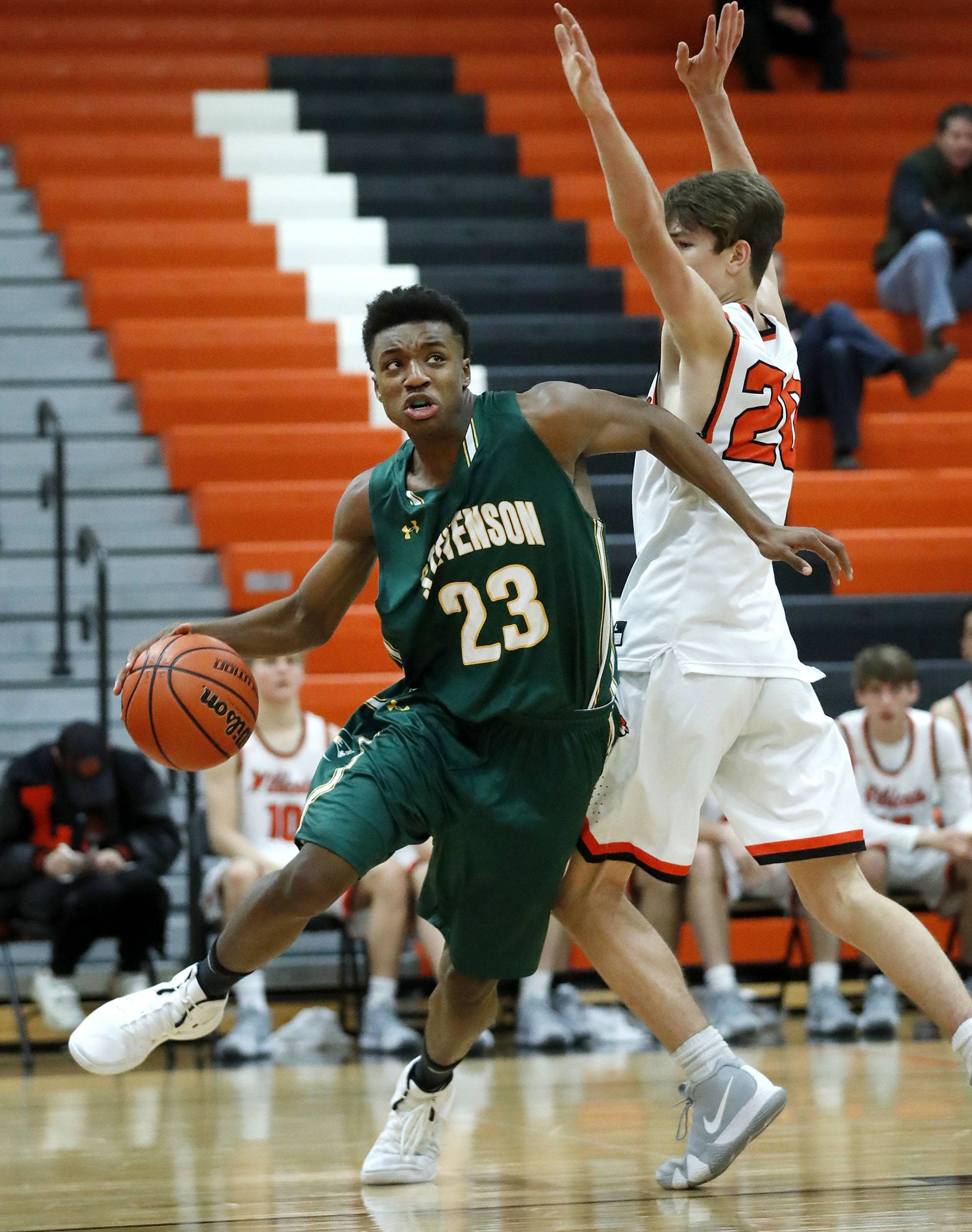 Stevenson's RJ Holmes (23) drives on Libertyville's Patrick Graham during their game Tuesday night in Libertyville.