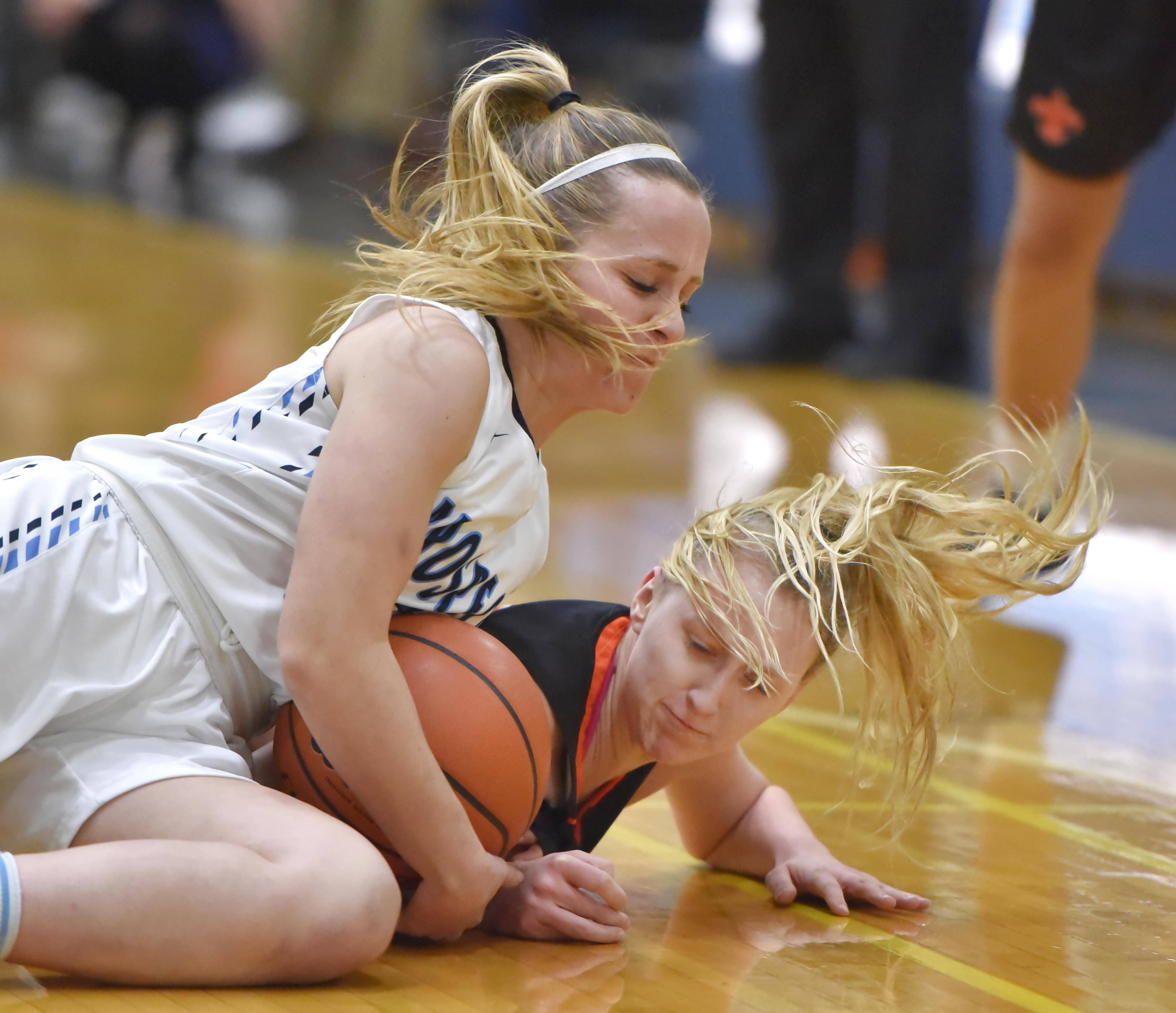 St. Charles East's Alexis Kiefer and Prospect's Helen Siavellis, left, battle for the ball Wednesday in a girls basketball game in Mount Prospect.