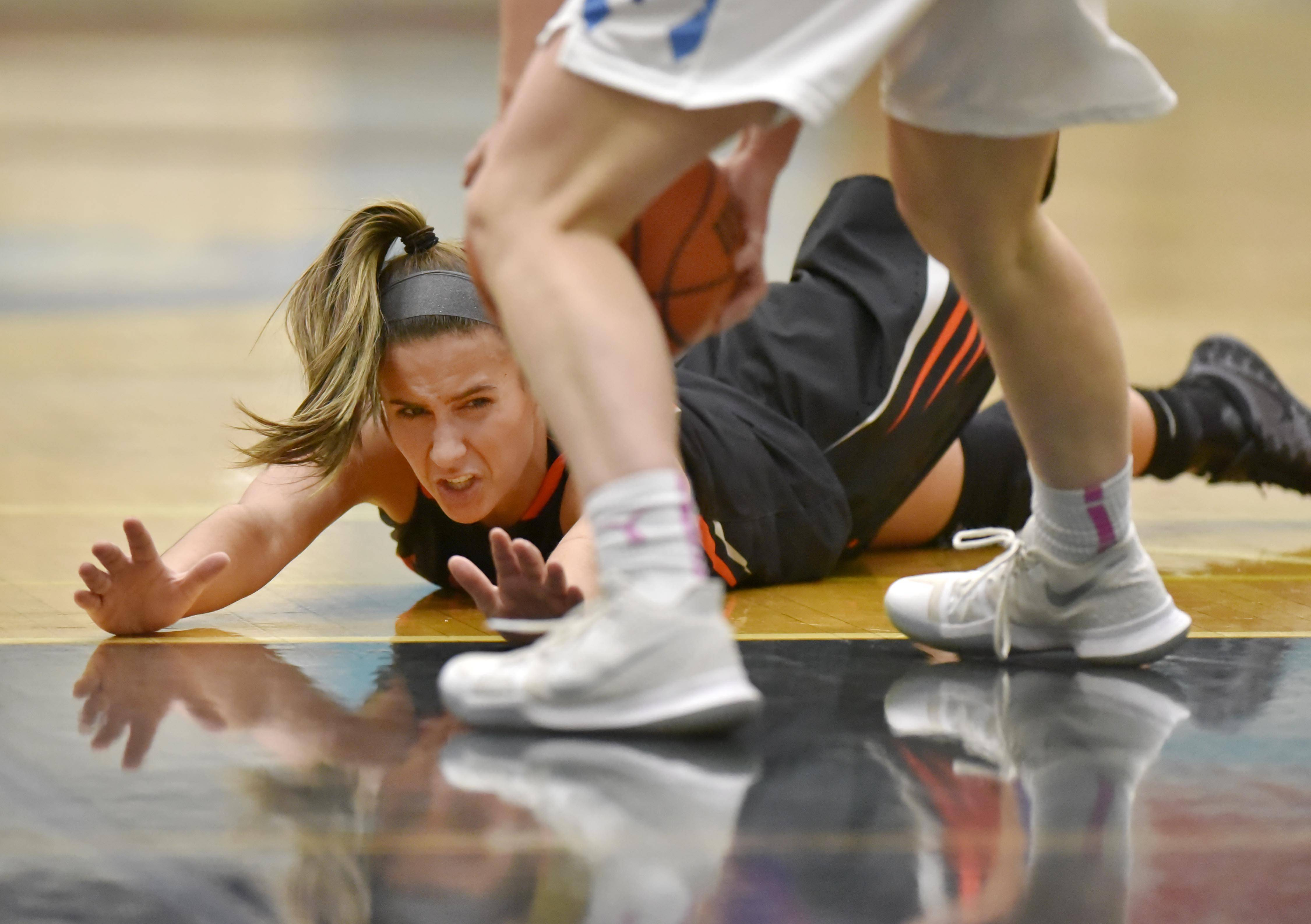 St. Charles East's Ashley DiOrio watches as Prospect's Ashley Adams picks up the ball she lost control of Wednesday in a girls basketball game in Mount Prospect.