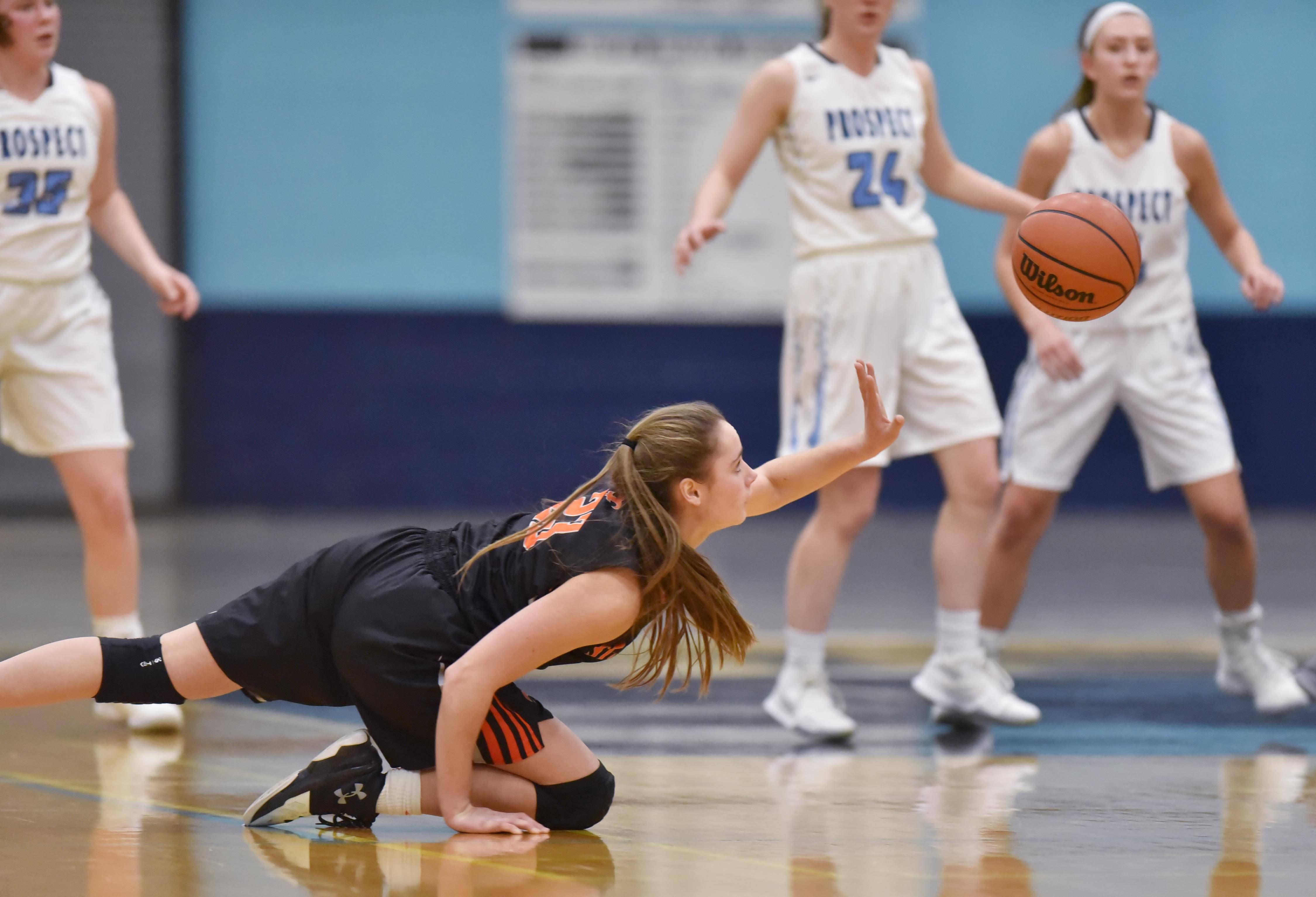 From the floor, St. Charles East's Makenna Brown slaps the ball to a teammate against Prospect Wednesday in a girls basketball game in Mount Prospect.