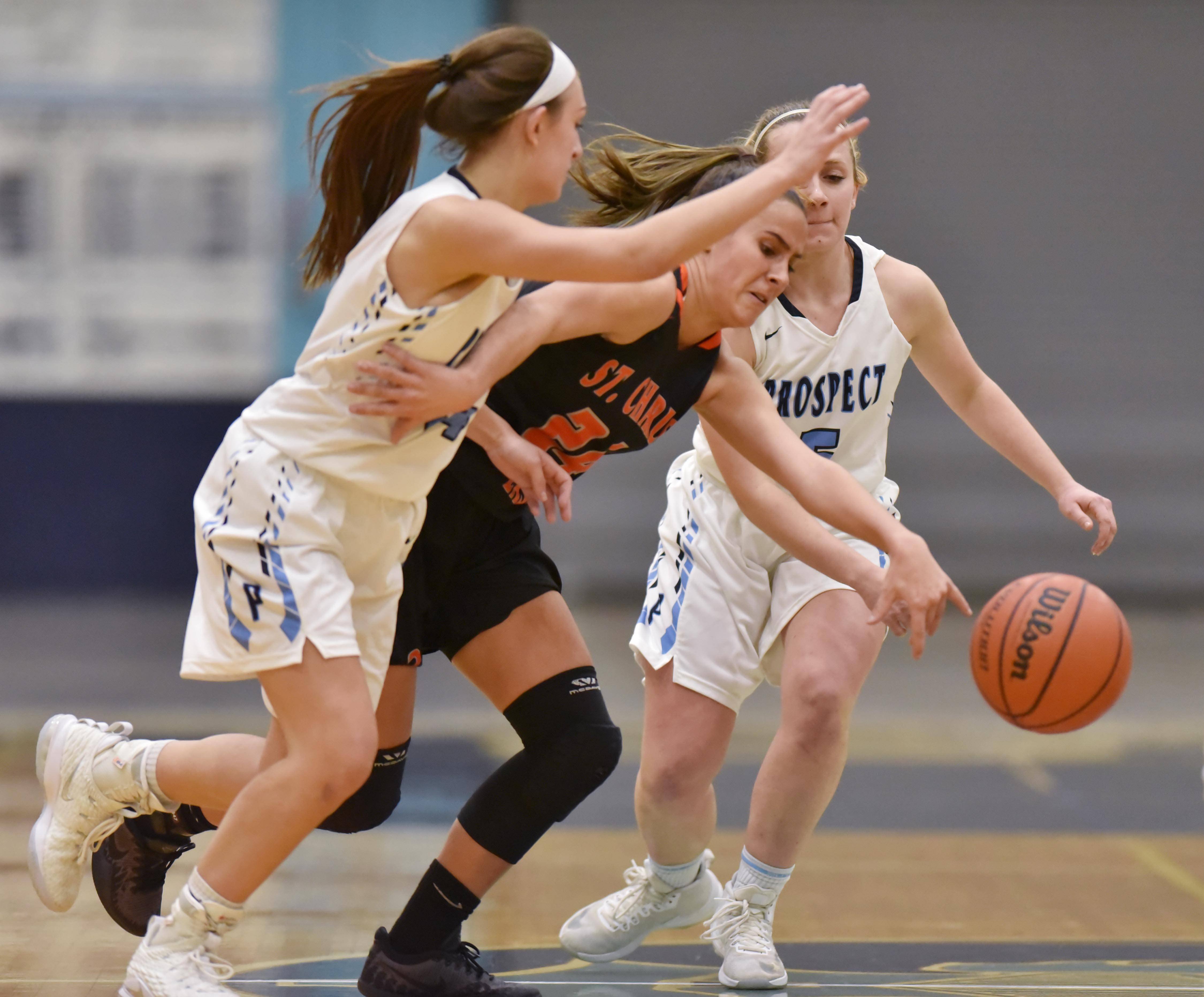 St. Charles East's Ashley DiOrio battles Prospect's Stephanie Kowalczyk and Helen Siavelis for the ball Wednesday in a girls basketball game in Mount Prospect.