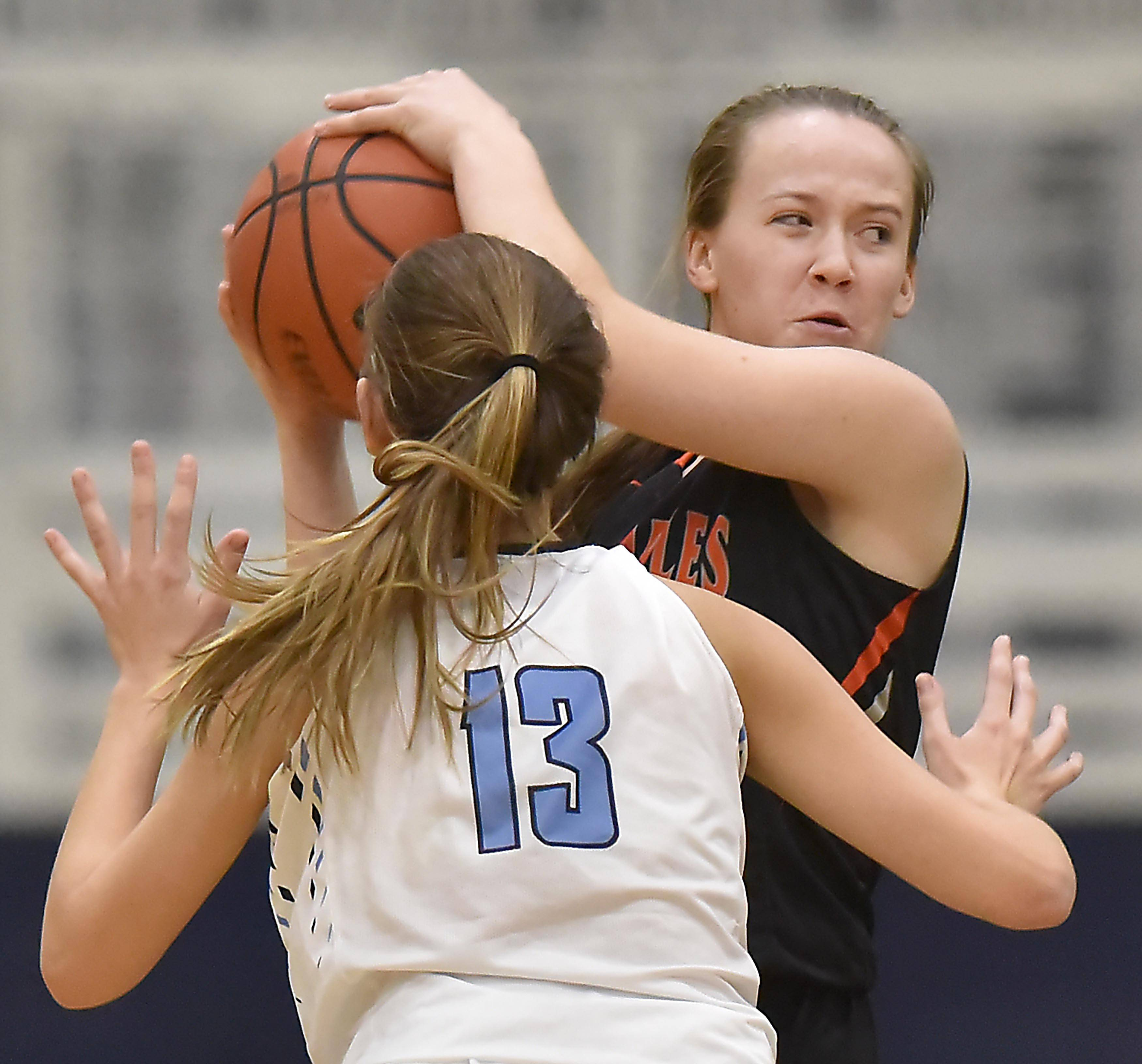 St. Charles East's Makenna Brown tries to find a teammate as Prospect's Jessica Kowalczyk pressures her Wednesday in a girls basketball game in Mount Prospect.