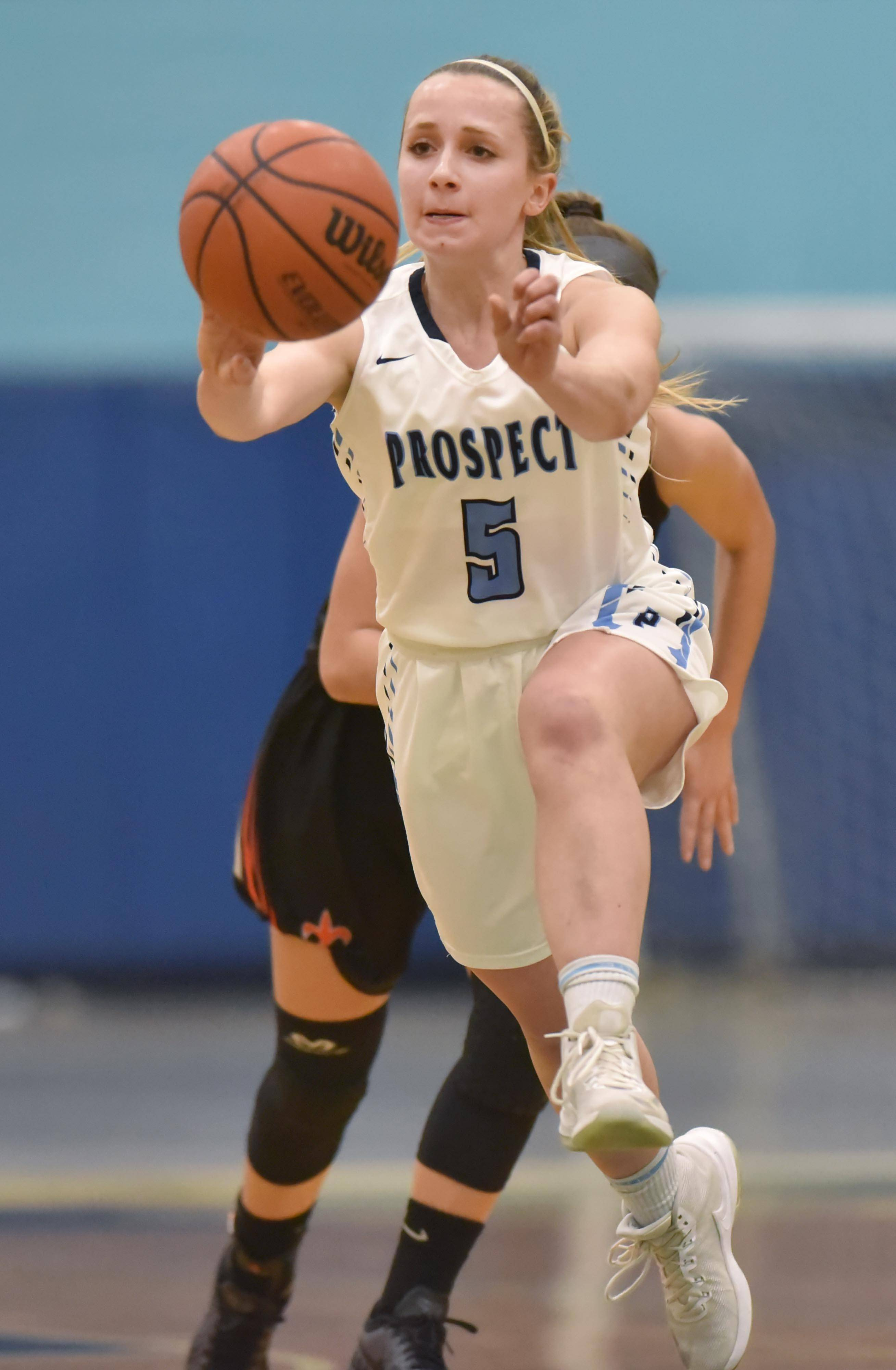 Prospect's Helen Siavelis heaves the ball to a teammate against St. Charles East Wednesday in a girls basketball game in Mount Prospect.