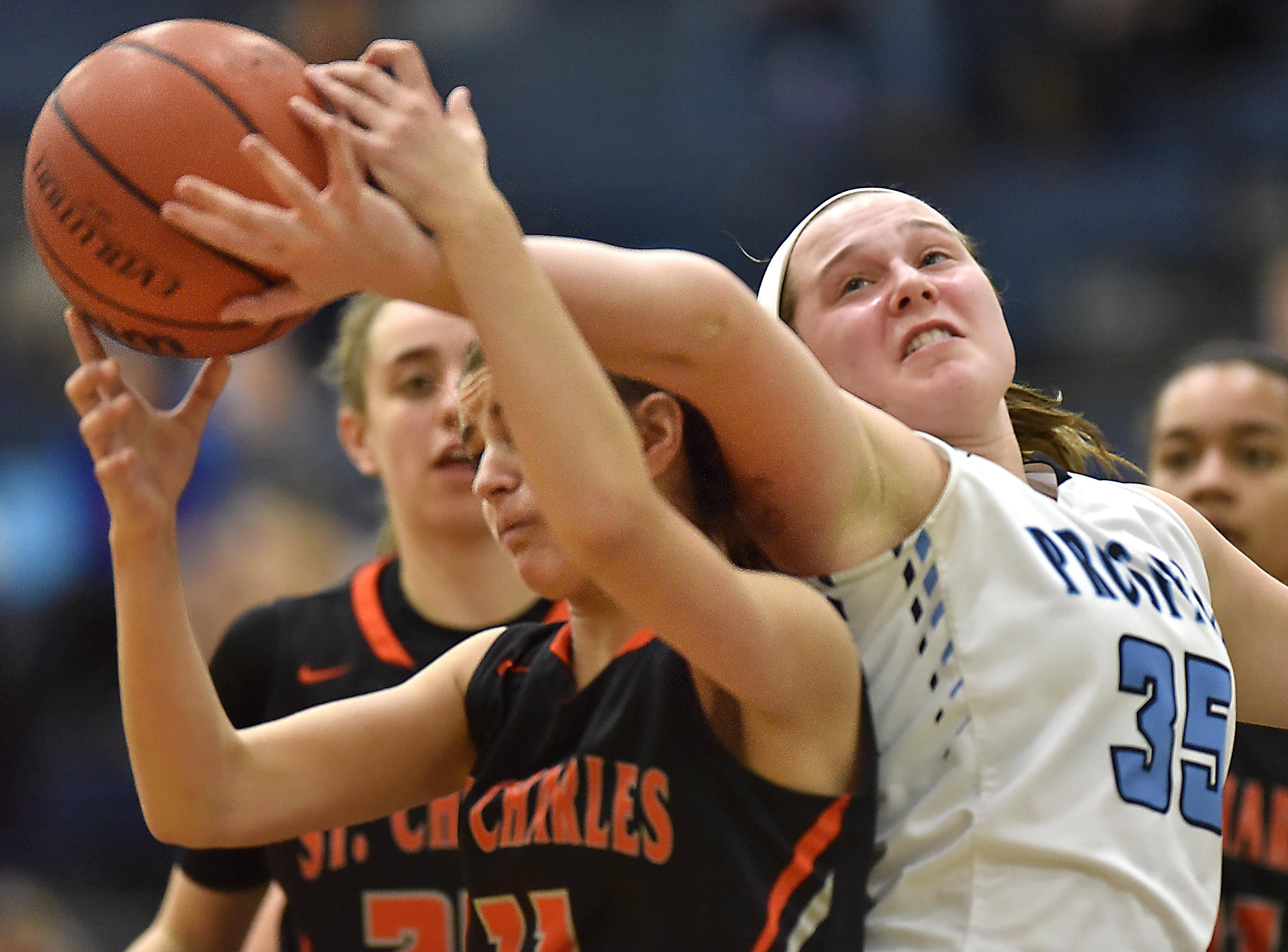 Prospect's Abbey Danciu extends her arm to keep St. Charles East's Victoria Kortan from getting a rebound Wednesday in a girls basketball game in Mount Prospect.