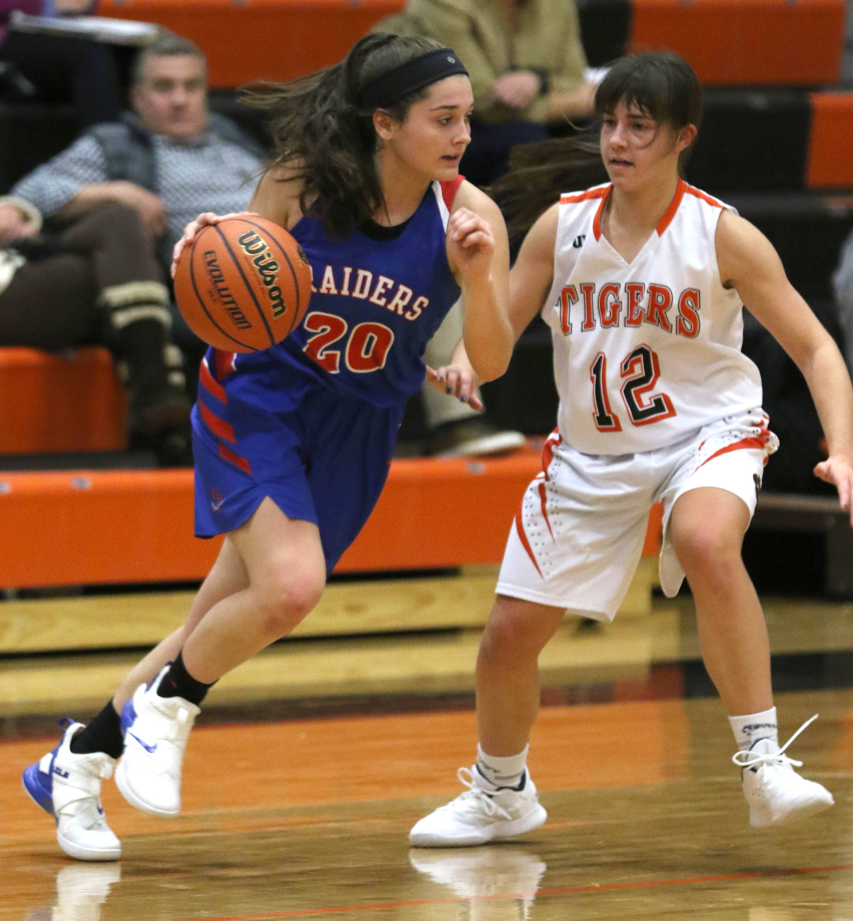 Glenbard South's Cat Karr, left, moves past Wheaton Warrenville South's Mira Emma during varsity girls basketball at Wheaton Warrenville South High School Wednesday evening.