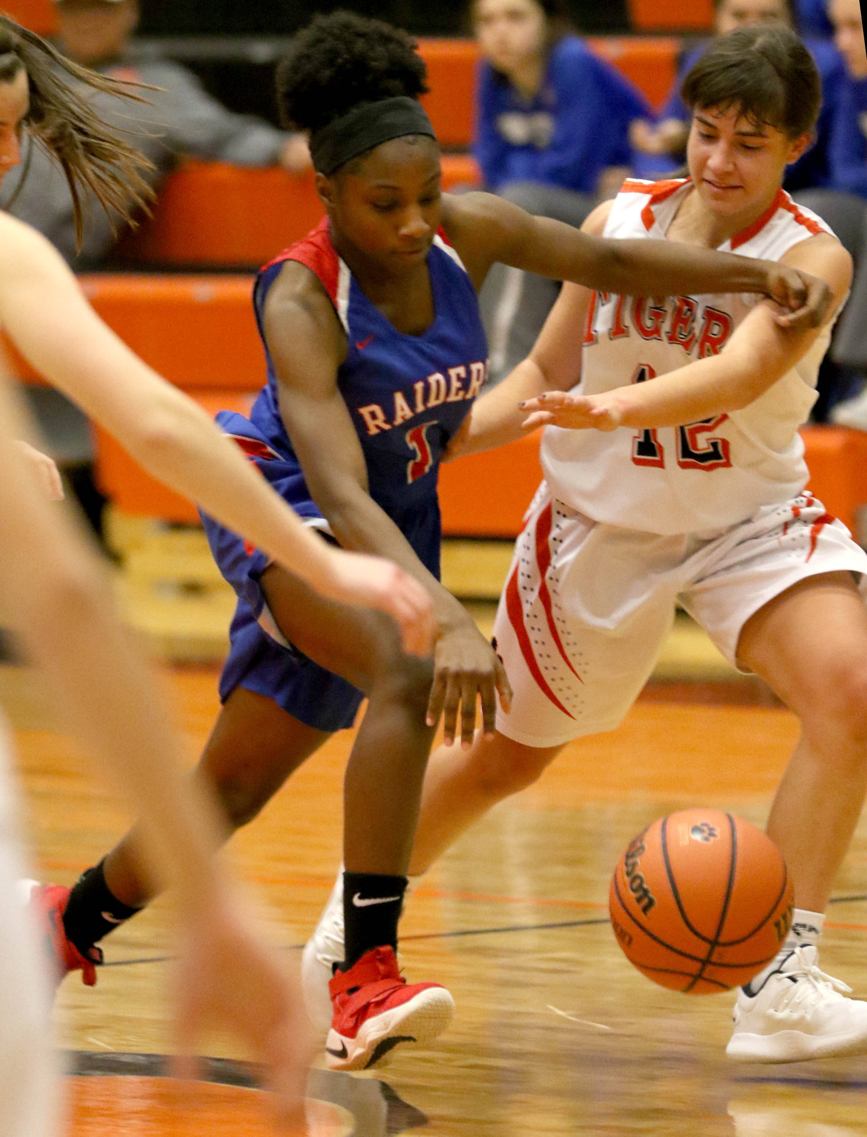 Glenbard South's India Lucas, center, slips past Wheaton Warrenville South's Mira Emma during varsity girls basketball at Wheaton Warrenville South High School Wednesday evening.