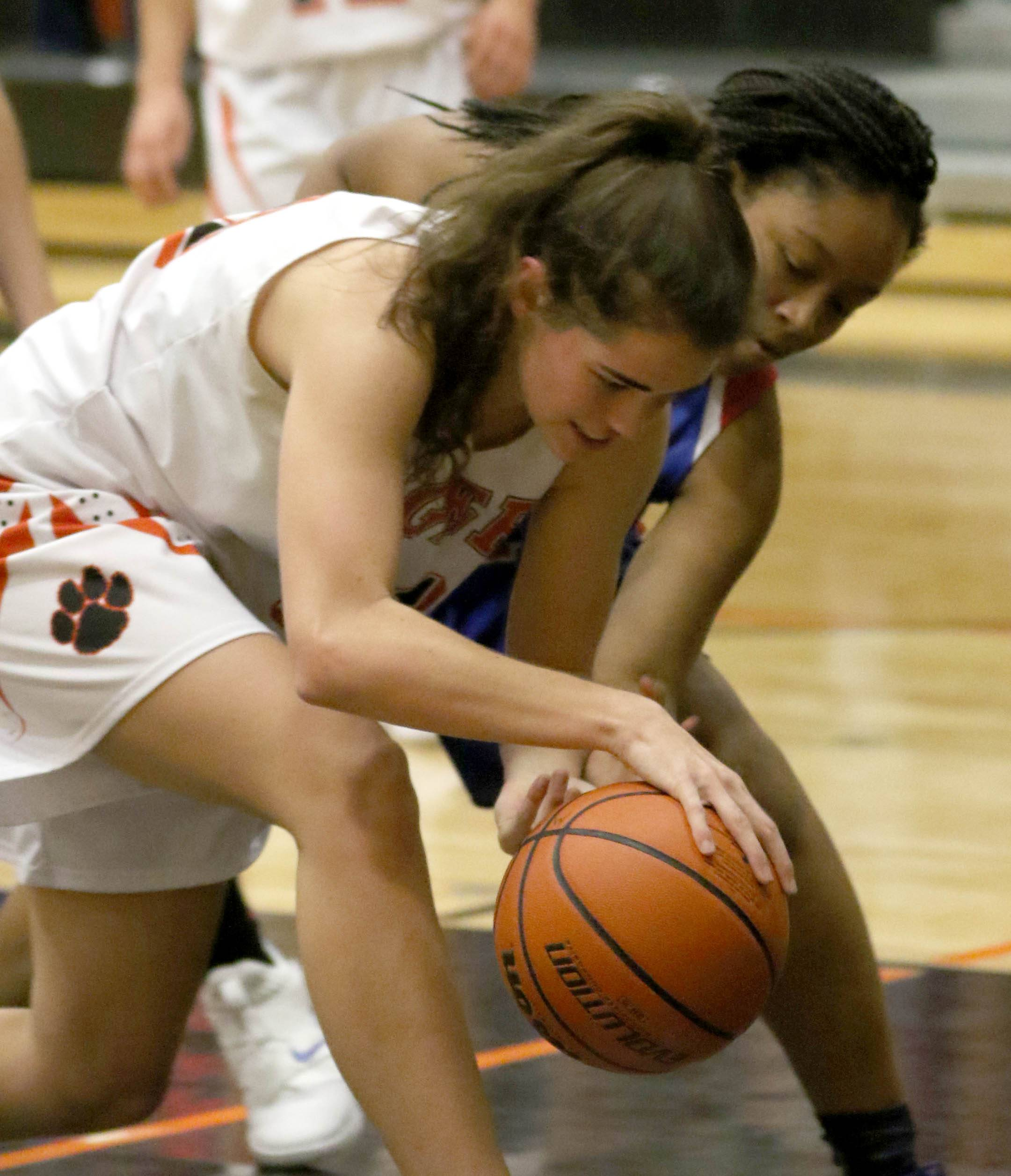 Glenbard South's Kori Willison, far, and Wheaton Warrenville South's MacKenzie Stebbins race to the ball during varsity girls basketball at Wheaton Warrenville South High School Wednesday evening.
