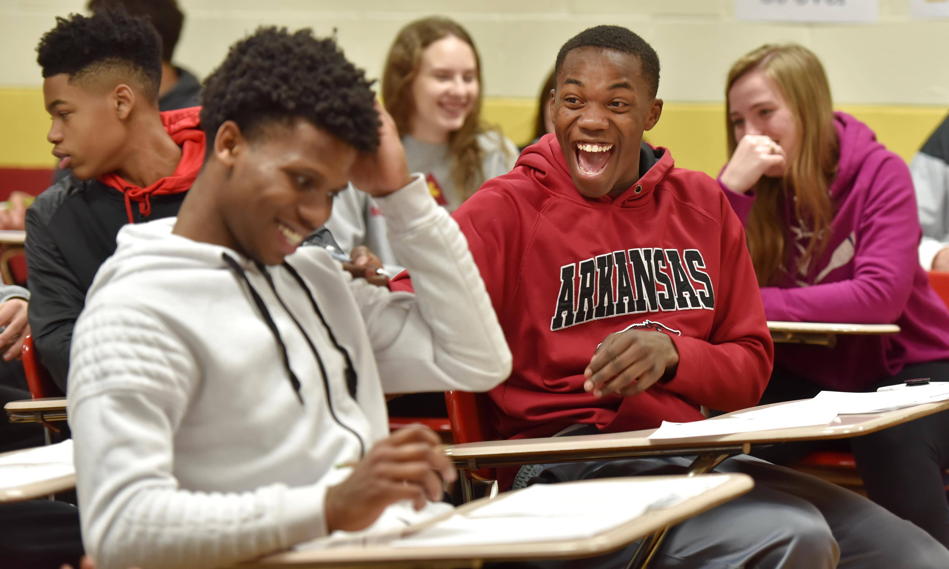Schaumburg High School boys basketball team members Heze Trotter, right, and Mike Hodges laugh as they relax and share ideas for their letters to U.S. service members. The team listened to U.S. Army Sgt. Ramiro Sanchez, who is stationed in the area. He spoke about the joy of receiving letters while on duty.