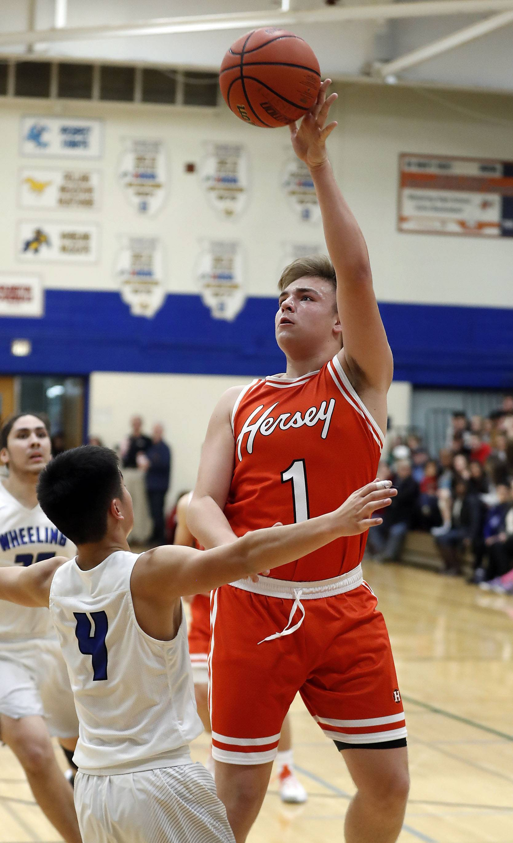 Hersey's Jacob Kluczewski (1) shoots over Wheeling's Jeremy Kim during their game Friday at Wheeling High School.