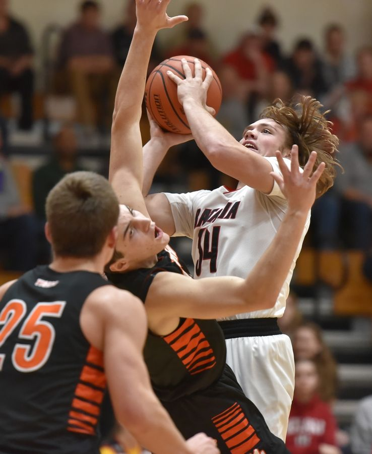 Batavia's Quin Urwiler drives into Wheaton Warrenville South's Matt Scherrman in a boys basketball game in Batavia Friday.
