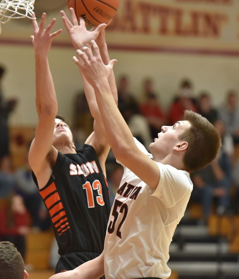 Batavia's Marko Yager gets a rebound as Wheaton Warrenville South's Matt Scherrman gets his finger caught in the net in a boys basketball game in Batavia Friday.