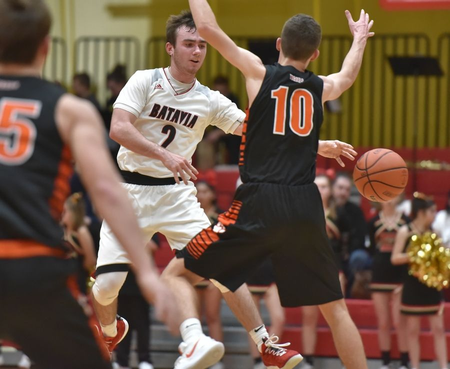 Batavia's Jack Carlson passes around Wheaton Warrenville South's Jeff Kratz in a boys basketball game in Batavia Friday.
