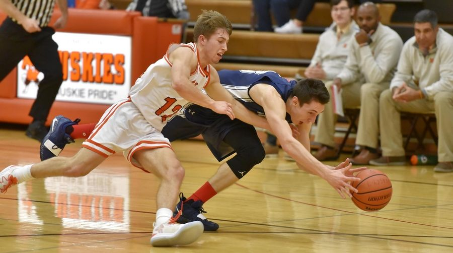 Hersey's Matt Hanushewsky and St. Viator's Connor Kuchera chase a loose ball Saturday in a boys basketball game in Arlington Heights.