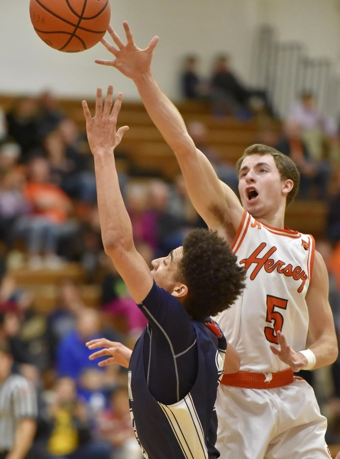 Hersey's Davis Belford tries to block a shot by St. Viator's Jeremiah Hernandez Saturday in a boys basketball game in Arlington Heights.