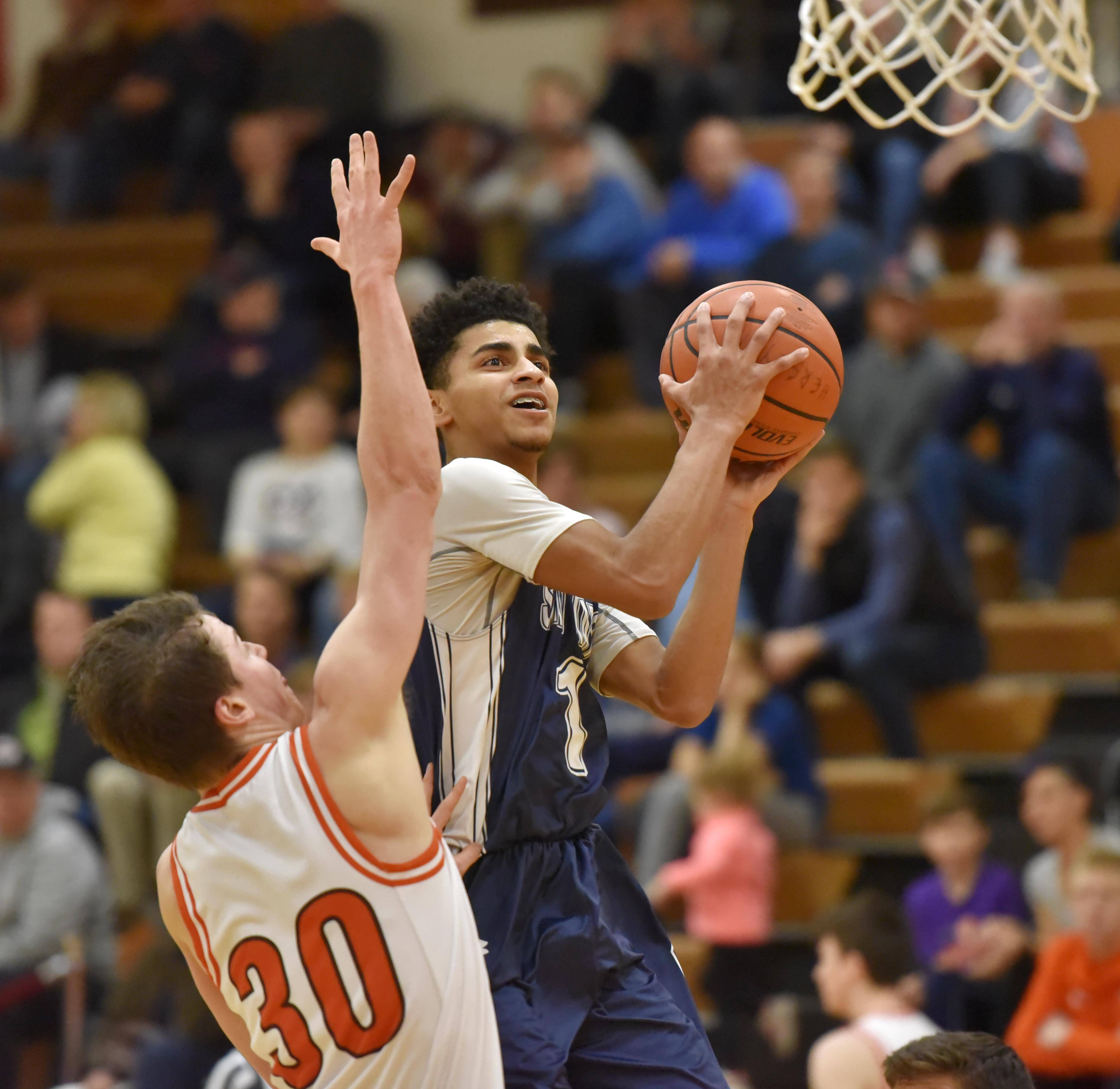 St. Viator's Treyvon Calvin glides past Hersey's Jason Schmidt Saturday in a boys basketball game in Arlington Heights.